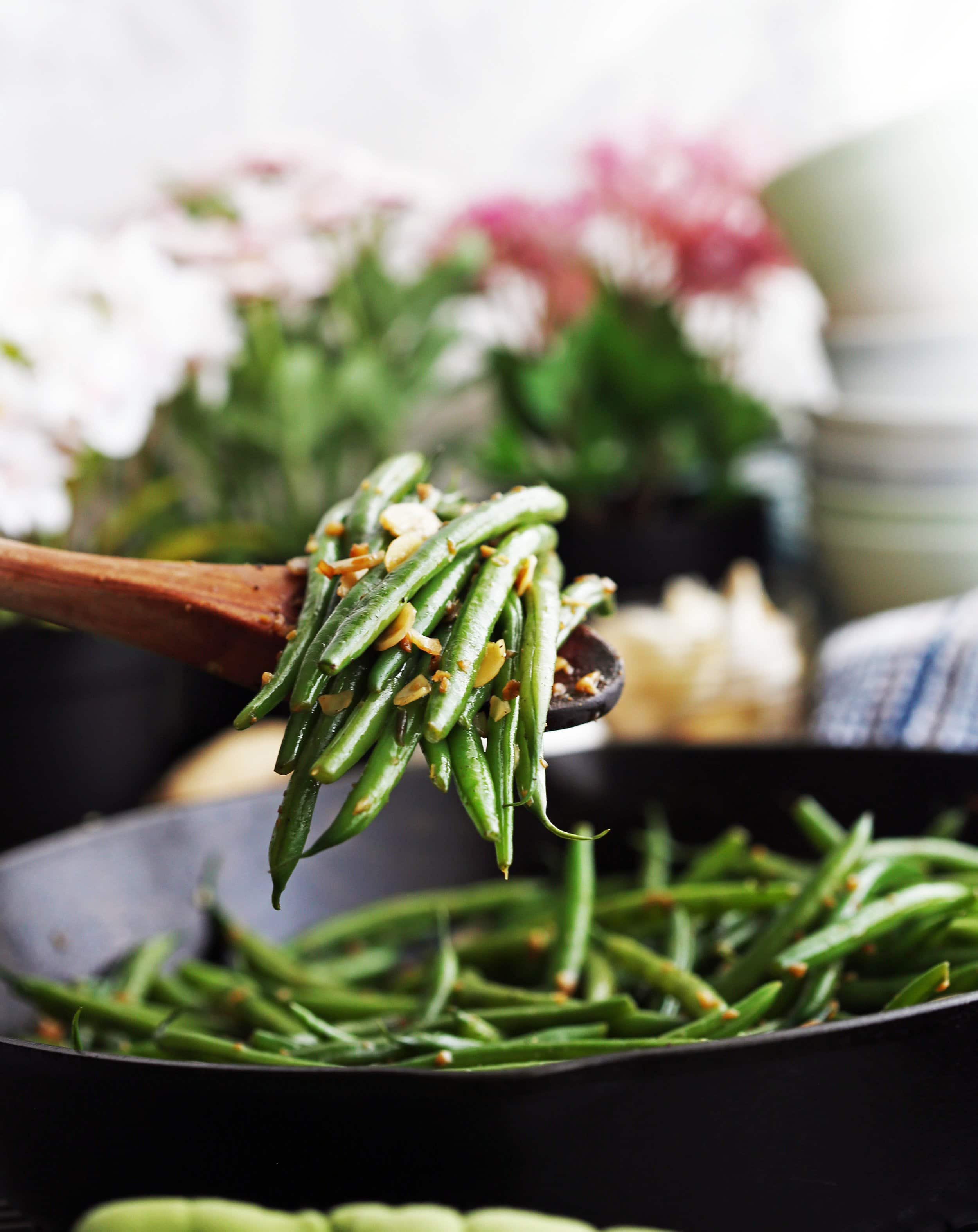 A large wooden spoon holding garlic ginger green beans with more green beans in a skillet in the background.