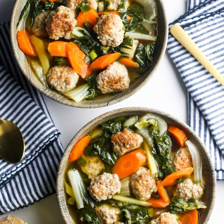 Overhead view of two wooden bowls filled with ginger pork meatball soup with bok choy and carrots.