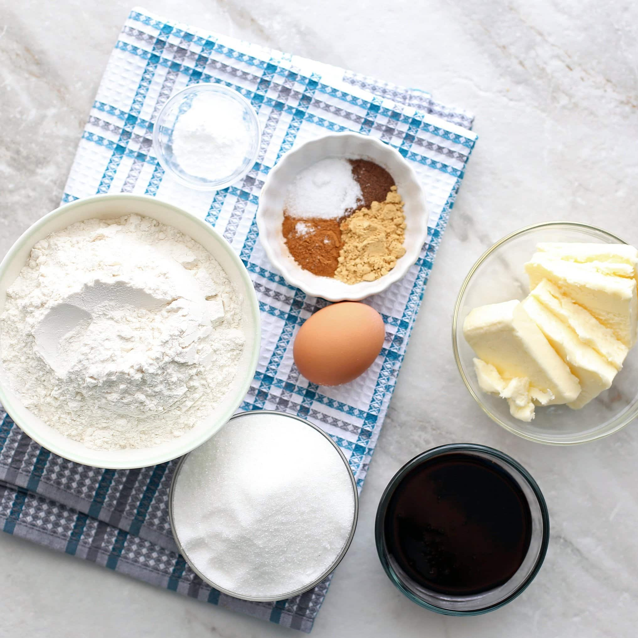Overhead view of a flour mixture,sugar, egg, molasses, butter, baking soda, and spices.