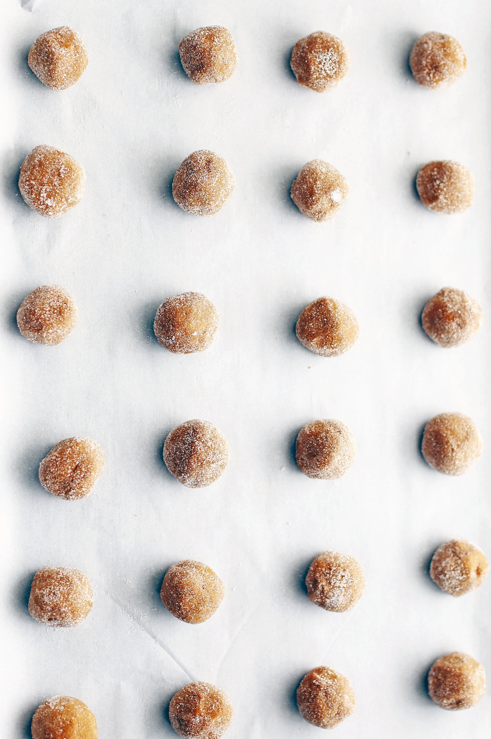 Tablespoon balls of gingersnap cookie dough rolled in sugar on a parchment lined baking sheet.