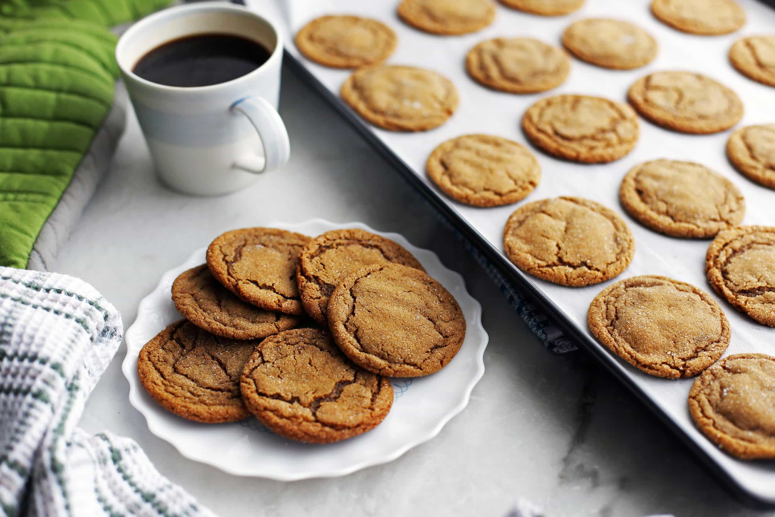 A plate full of chewy gingersnap (ginger molasses) cookies with more cookies on a baking sheet beside it.
