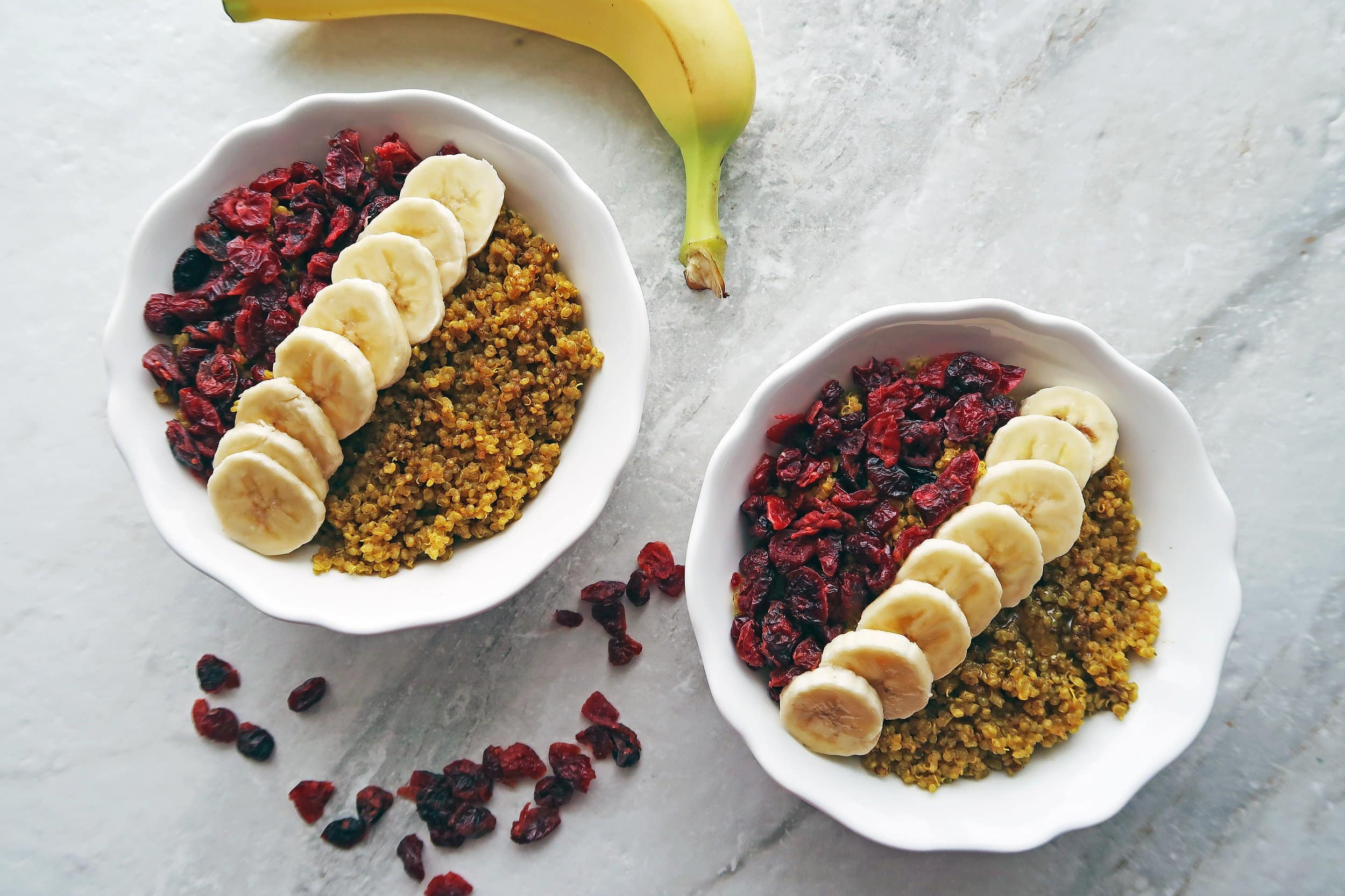 Two golden milk (turmeric latte) quinoa bowls garnished with dried cranberries and banana slices.