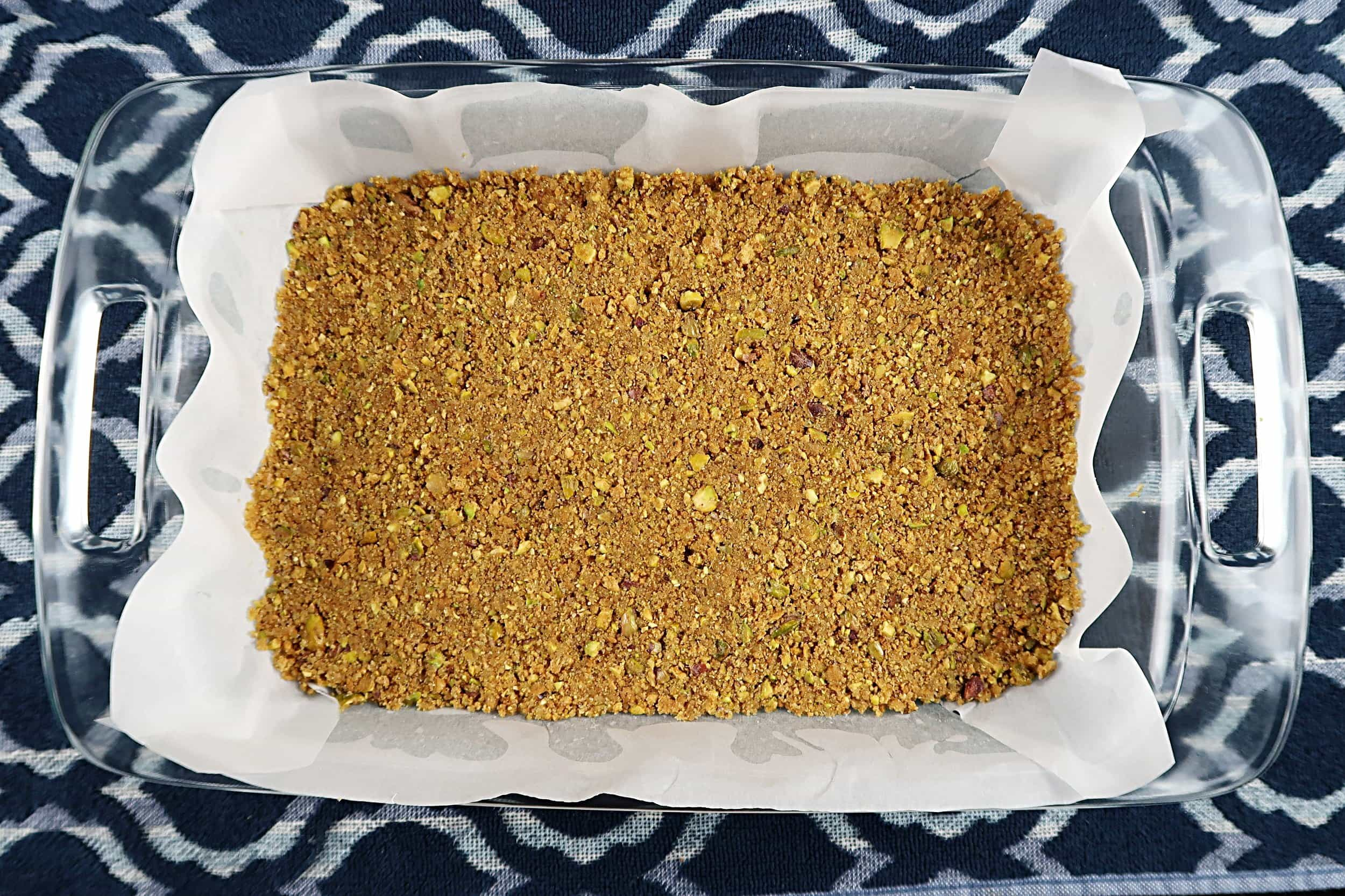 Pistachio and graham cracker crust pressed into a baking dish.