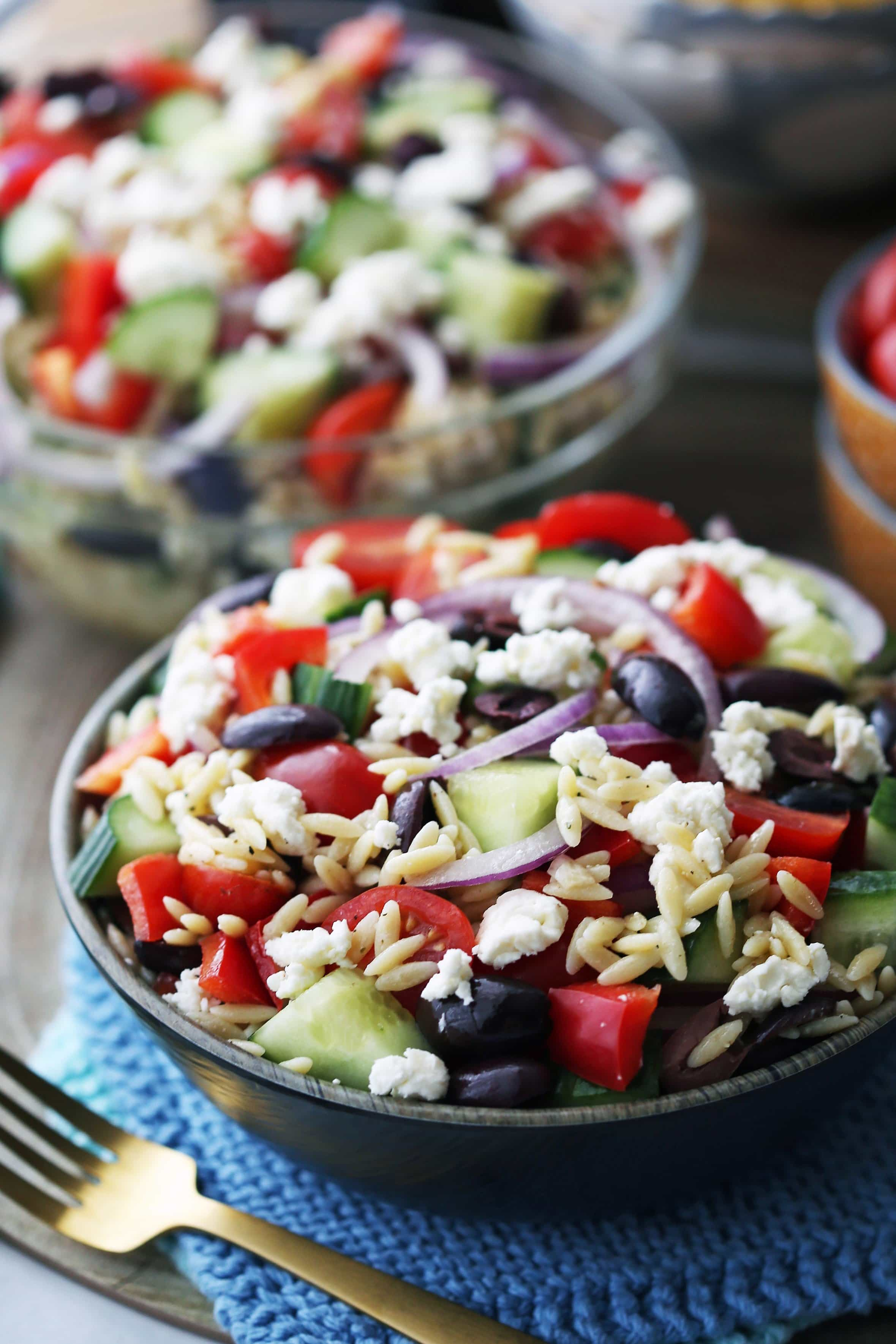 Greek orzo pasta salad with lemon vinaigrette in a brown bowl and in a large glass bowl.