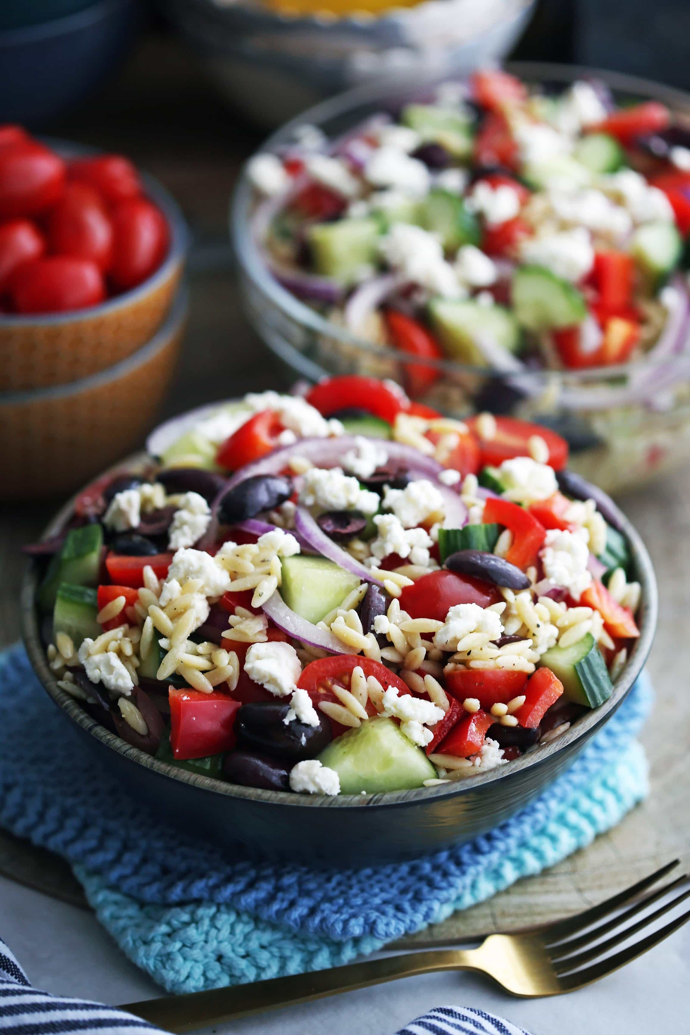 Greek orzo salad with crumbled feta, Kalamata olives, and raw vegetables in a dark brown bowl and a large glass bowl.