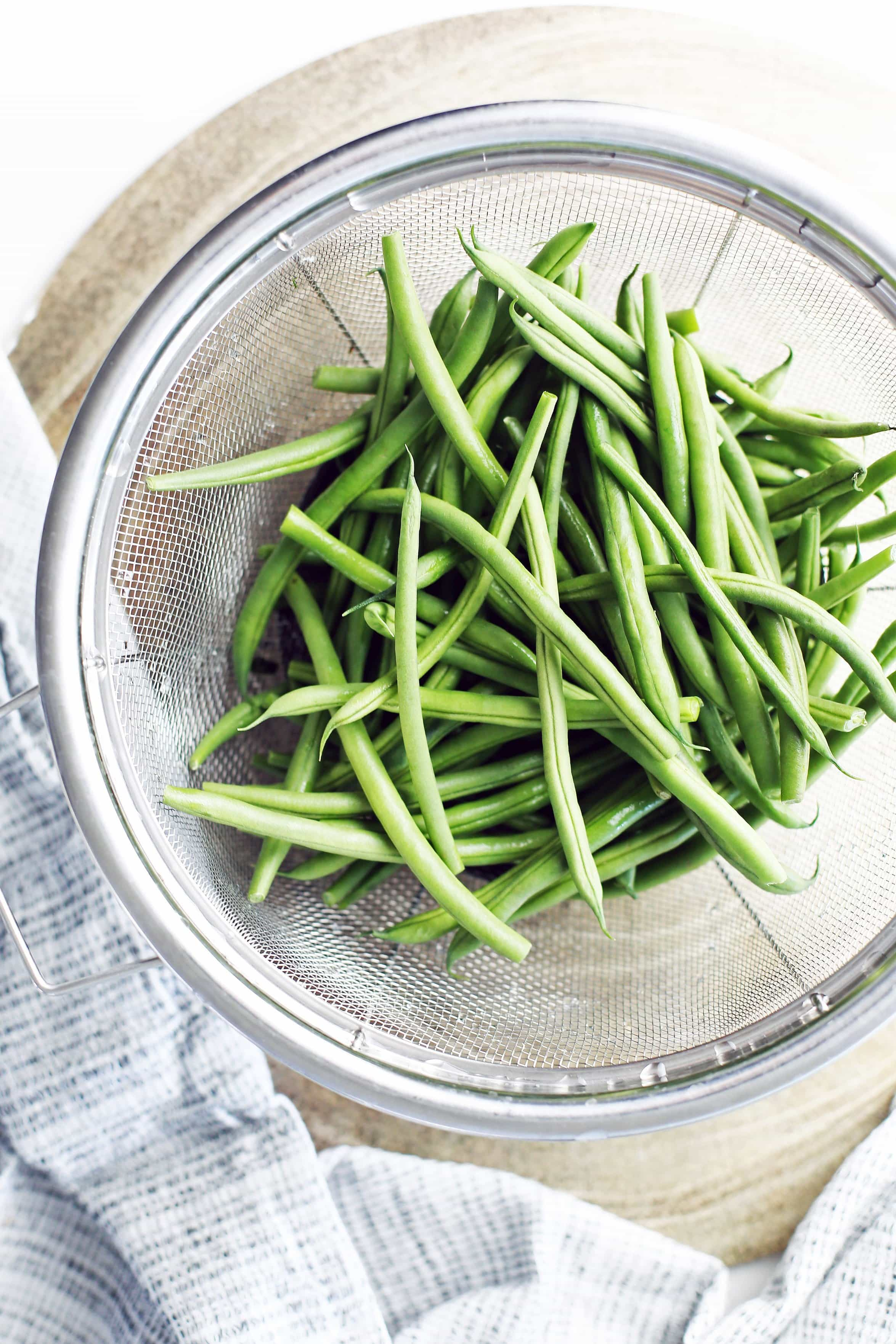 Overhead view of rinsed and trimmed French green beans in large metal mesh strainer.