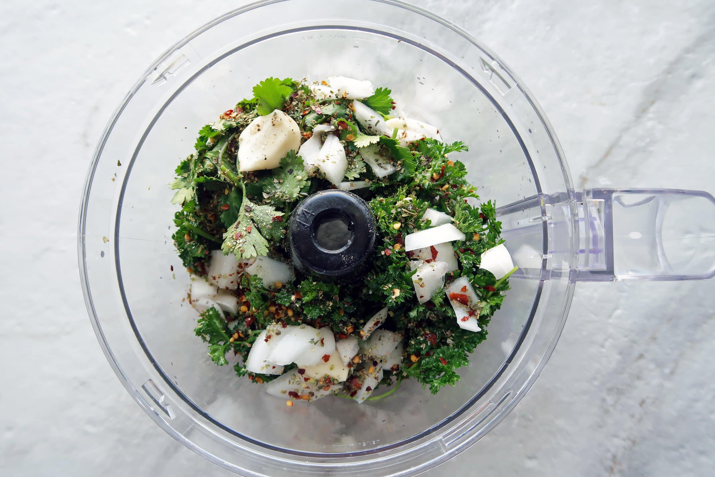 A food processor containing chimichurri sauce ingredients including parsley, garlic, and onion.