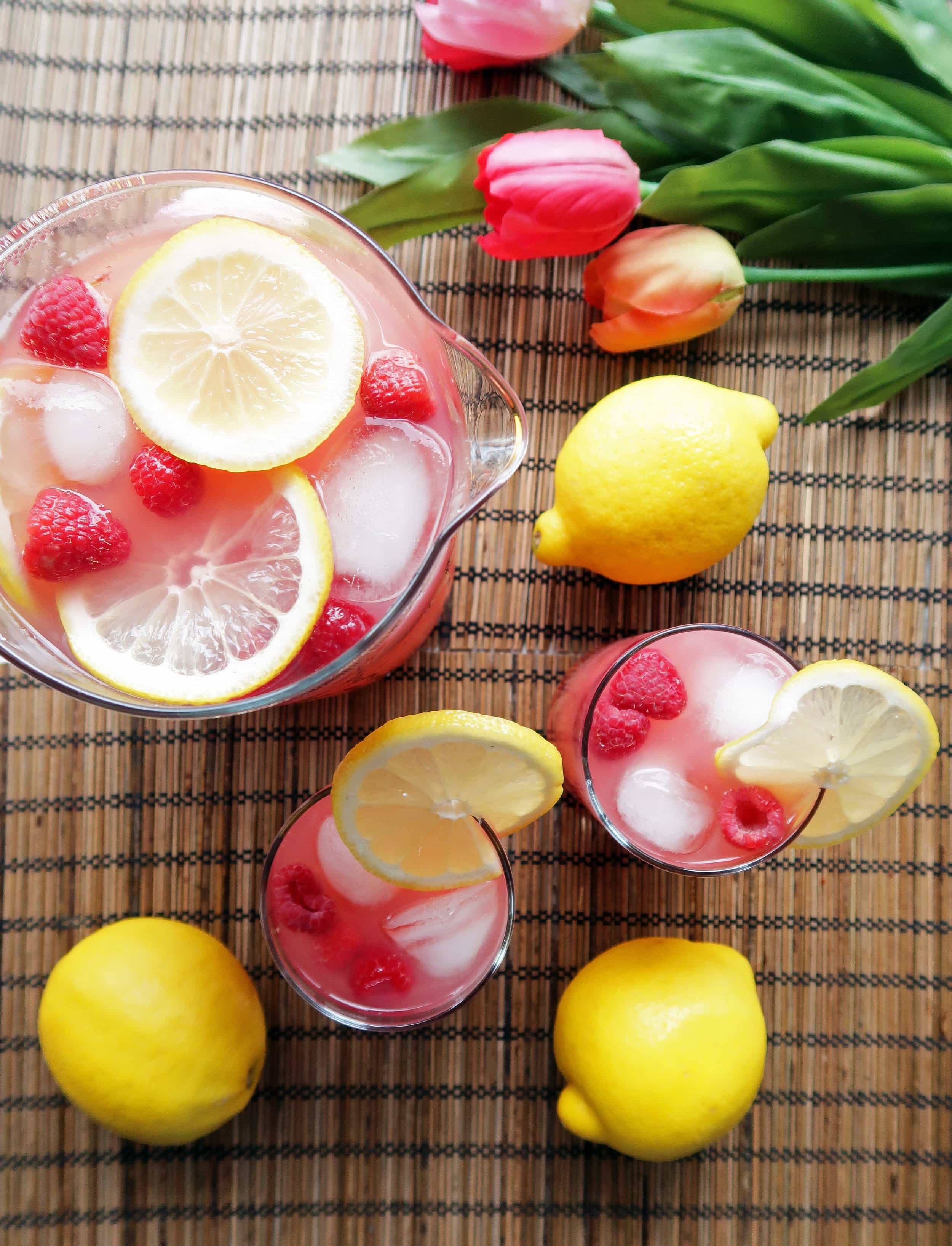 Two glasses and a pitcher full of homemade Raspberry Green Tea Lemonade with lemon slices and raspberry garnish