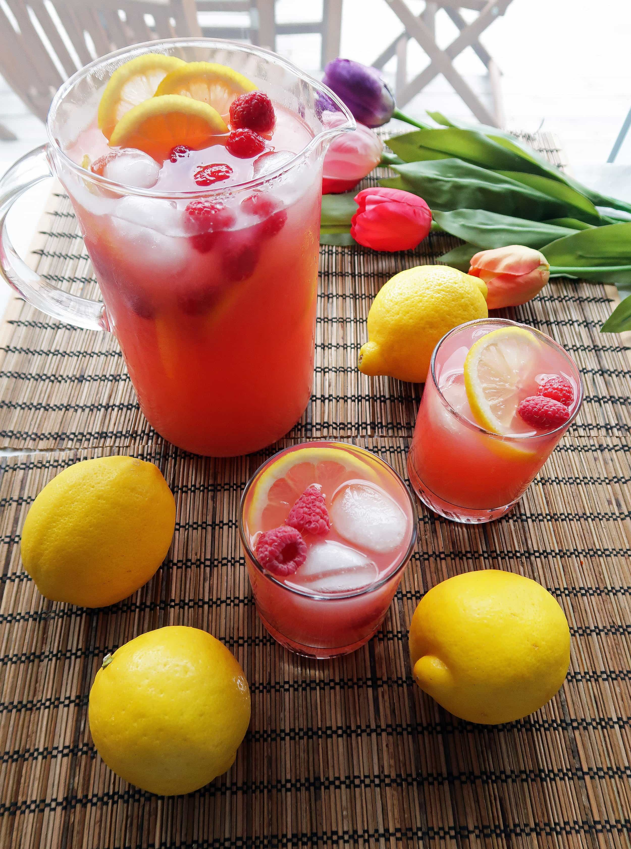 Two glasses and a pitcher full of homemade Raspberry Green Tea Lemonade with lemon slices and raspberry garnish; whole lemons around them.