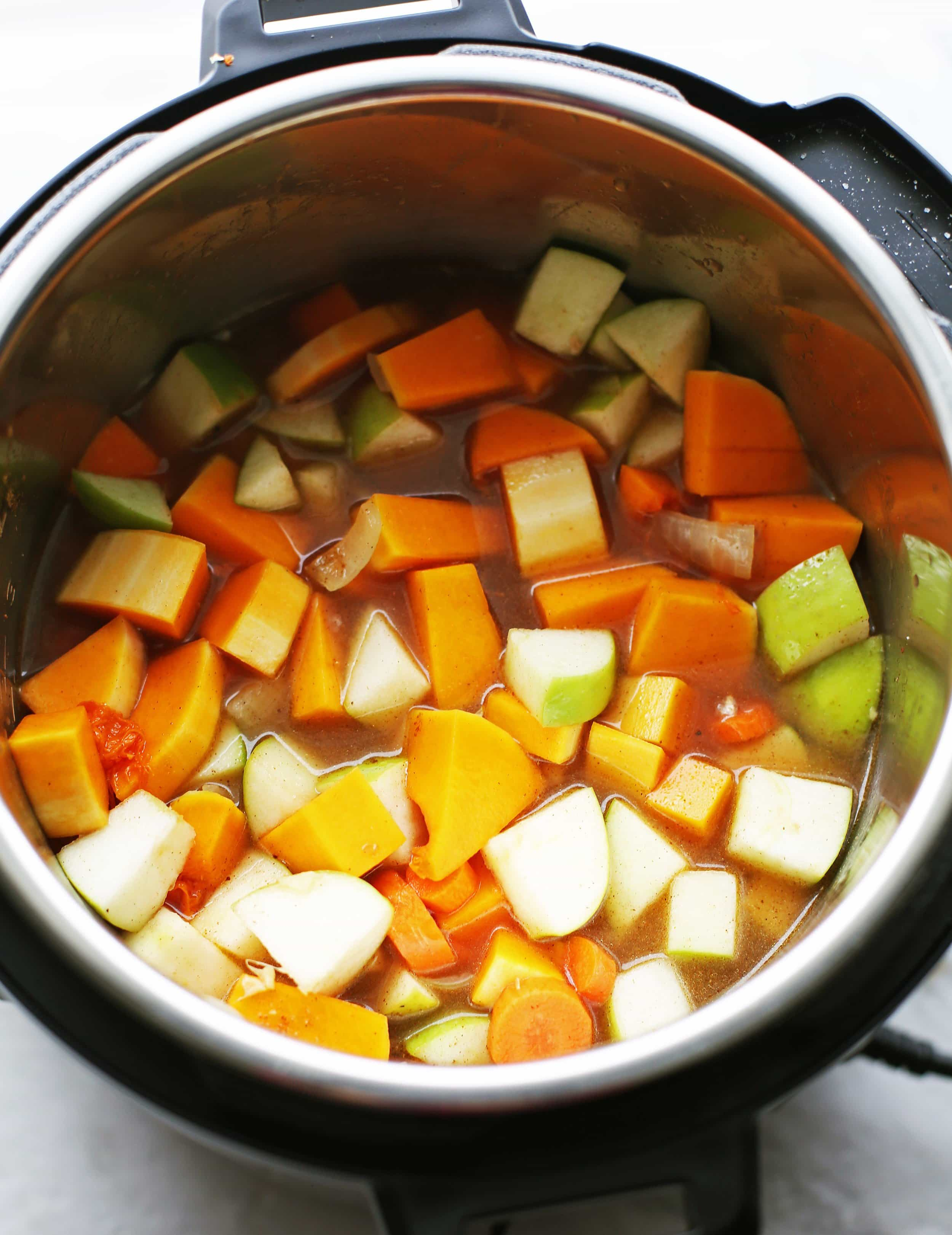 Sautéed onions, ginger, and garlic with chopped butternut squash, granny smith apples, carrots, spices, and vegetable broth are mixed in the Instant Pot.
