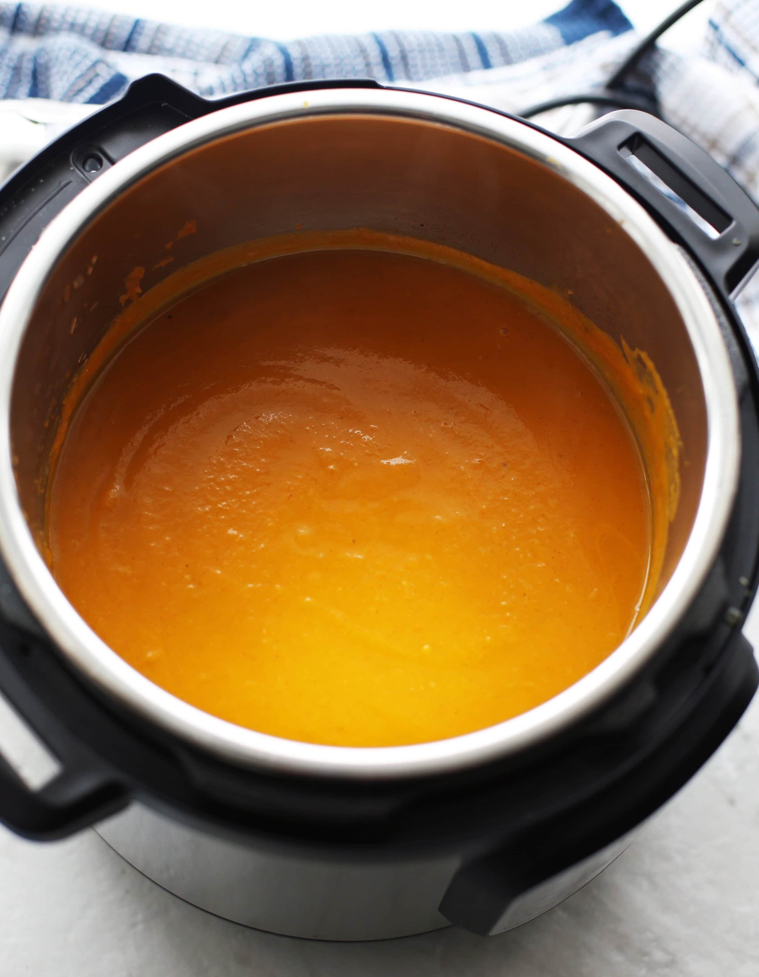 A vibrant orange pureed butternut squash apple ginger soup in the Instant Pot.