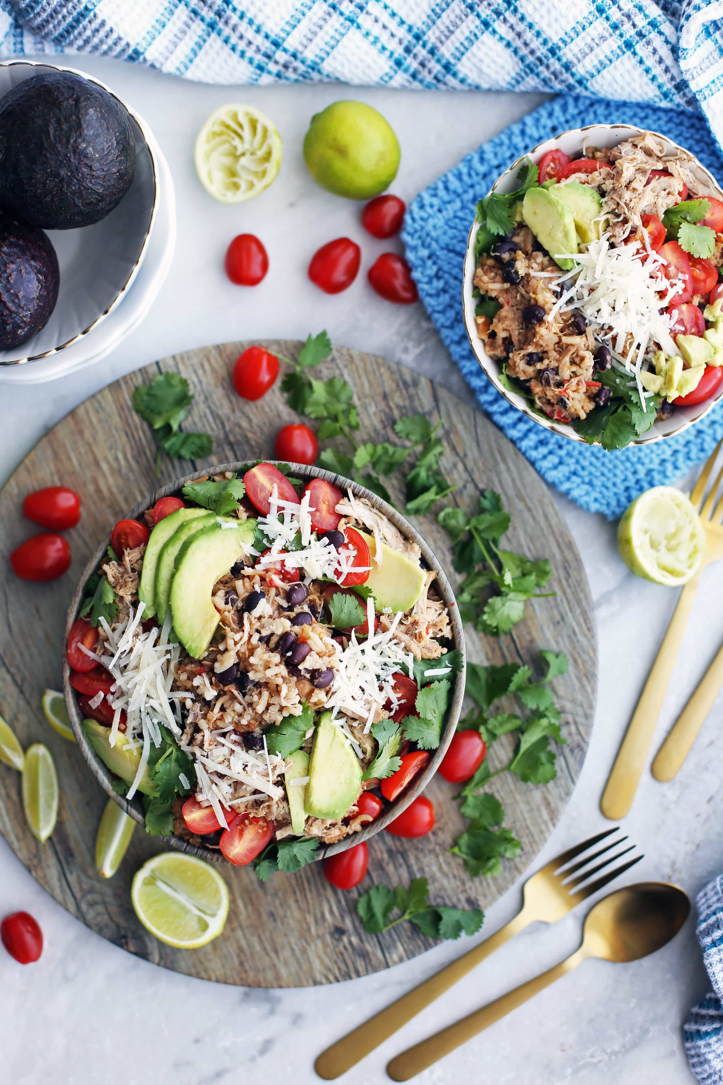 Overhead view of two Instant Pot Chicken and Rice Burrito Bowls topped and surrounded by limes, avocado, tomatoes, cheese, and cilantro.