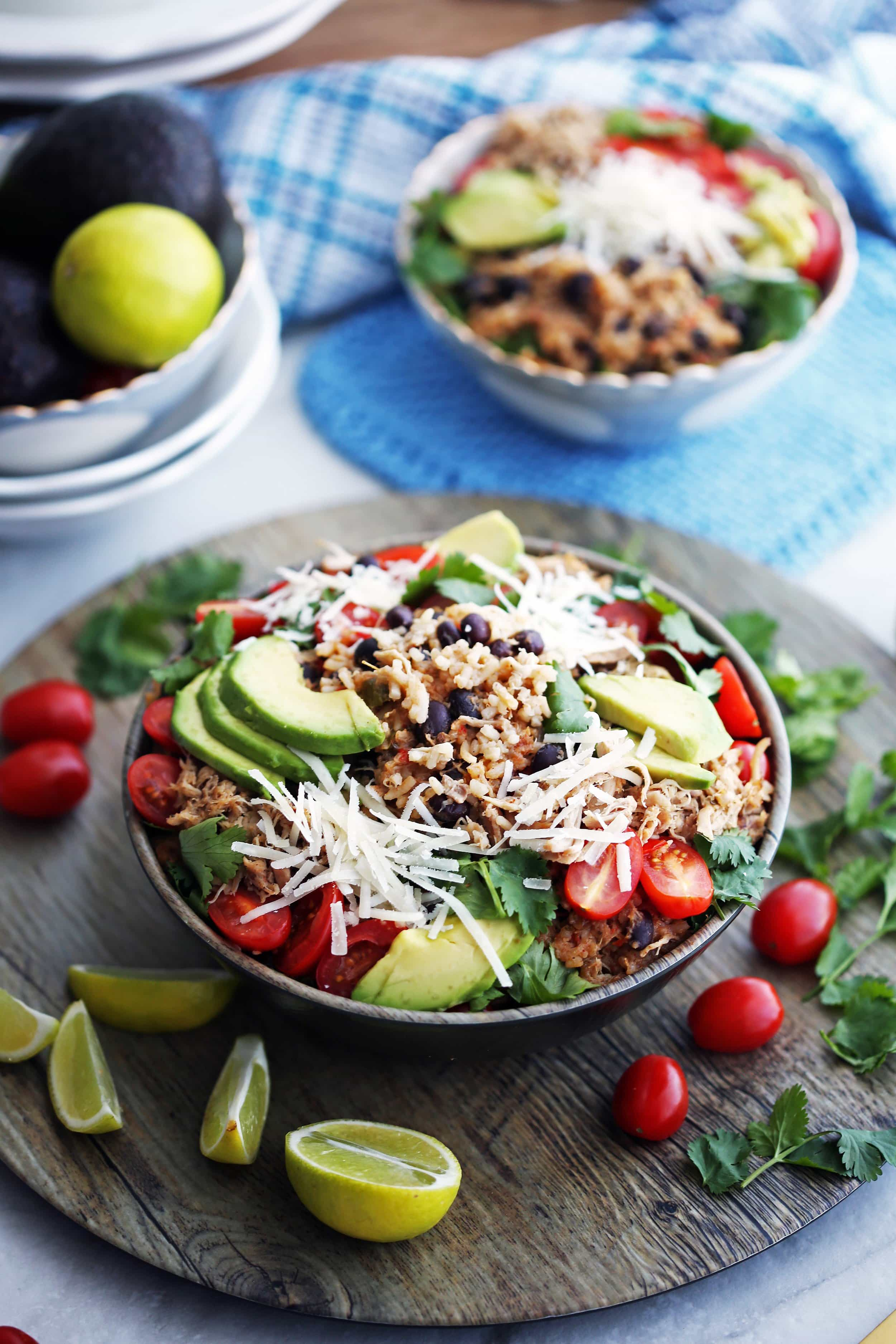 A full bowl of shredded chicken, black beans, and rice that's topped with avocado, cheese, tomatoes, and cilantro.
