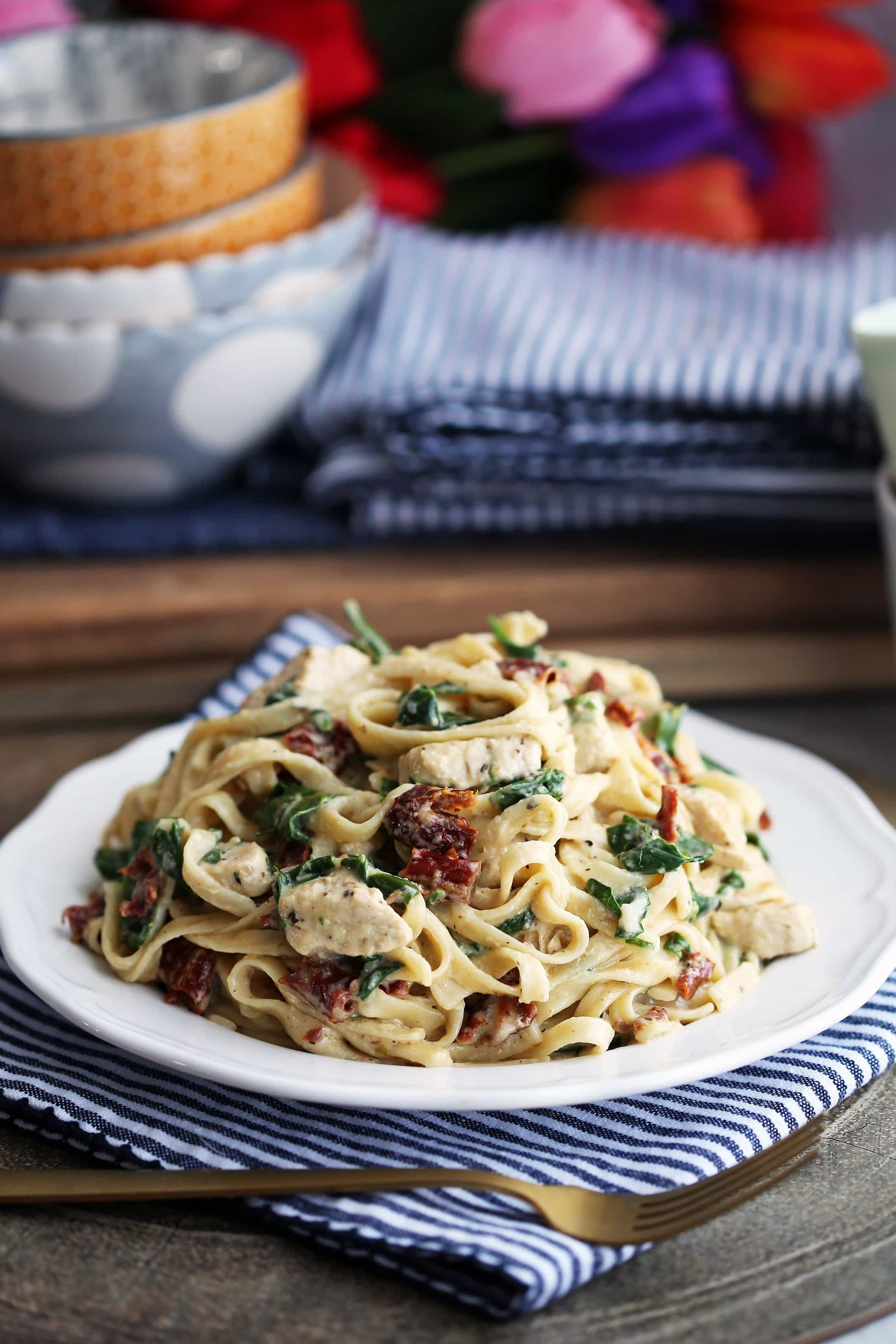 Instant Pot creamy fettuccine with chicken, spinach, and sun-dried tomatoes on a white plate.