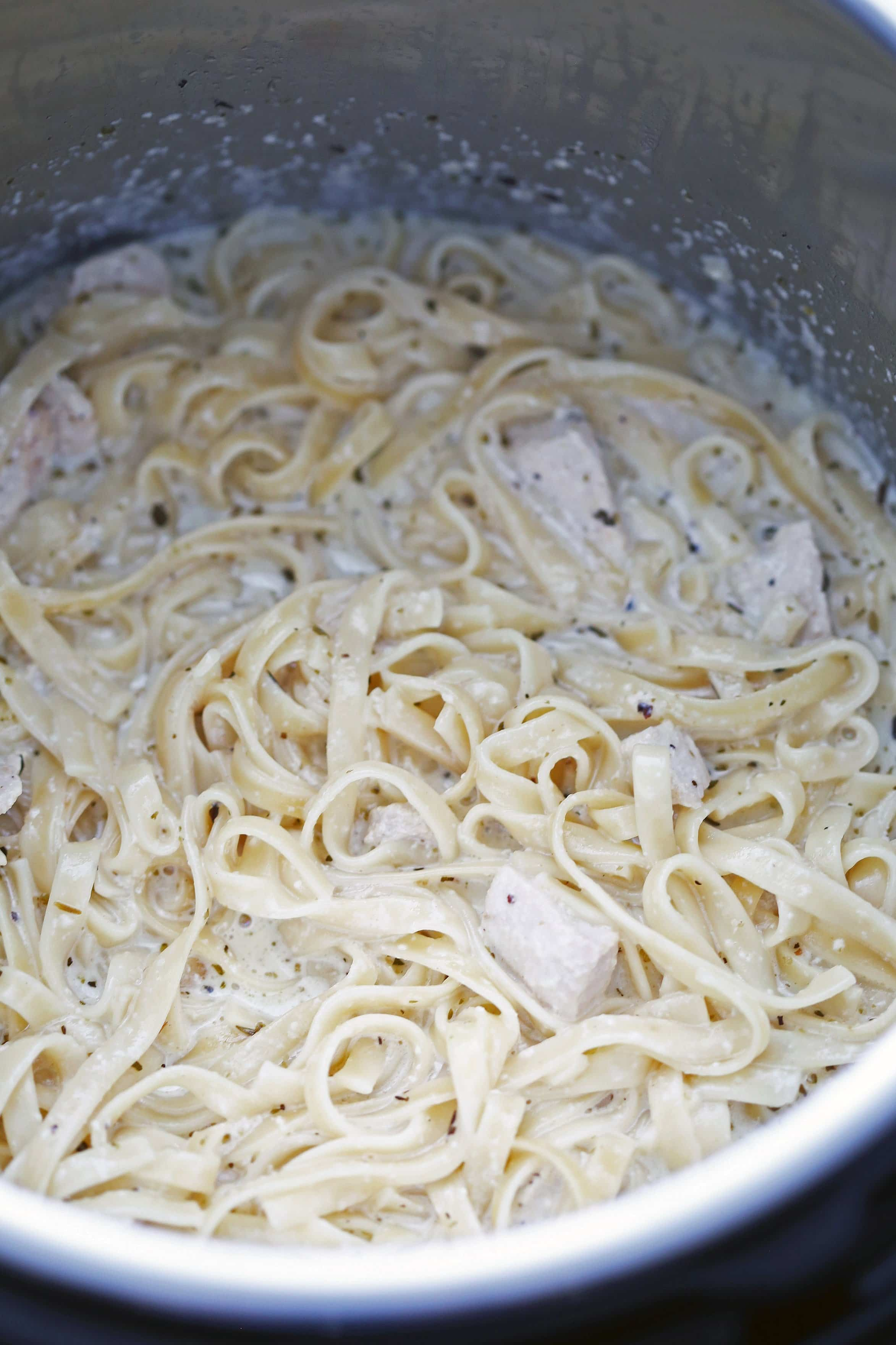 Cooked fettuccine pasta tossed in a cream sauce and diced chicken in the Instant Pot.