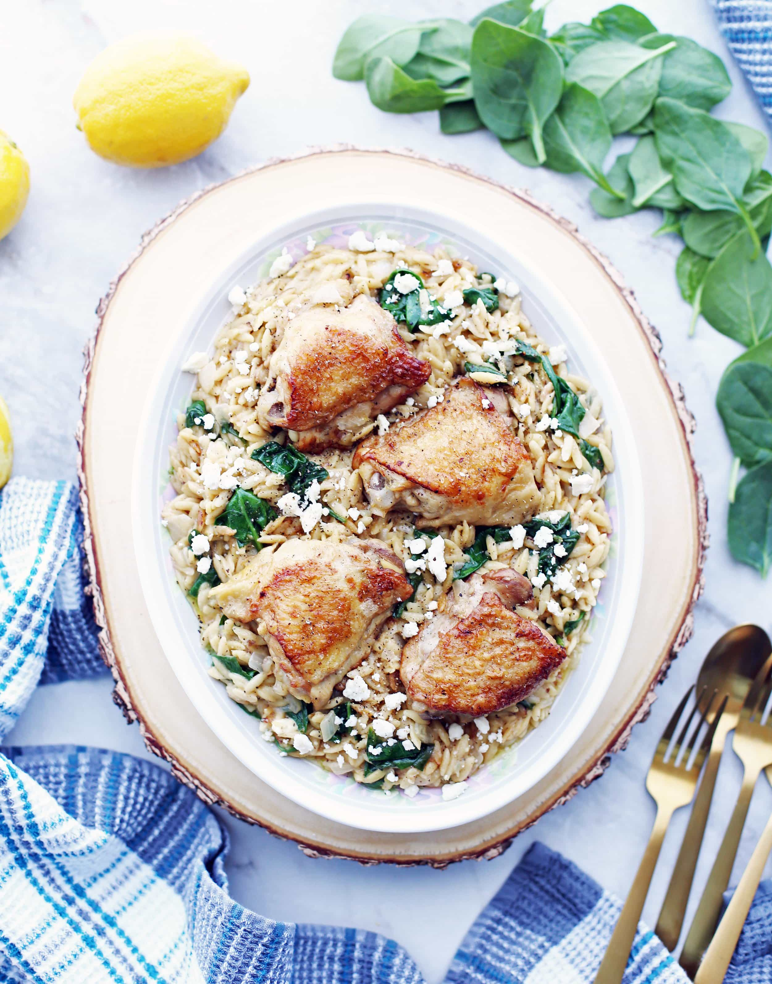 Cooked chicken thighs placed on top of lemon pepper orzo with feta and spinach on a large oval platter.