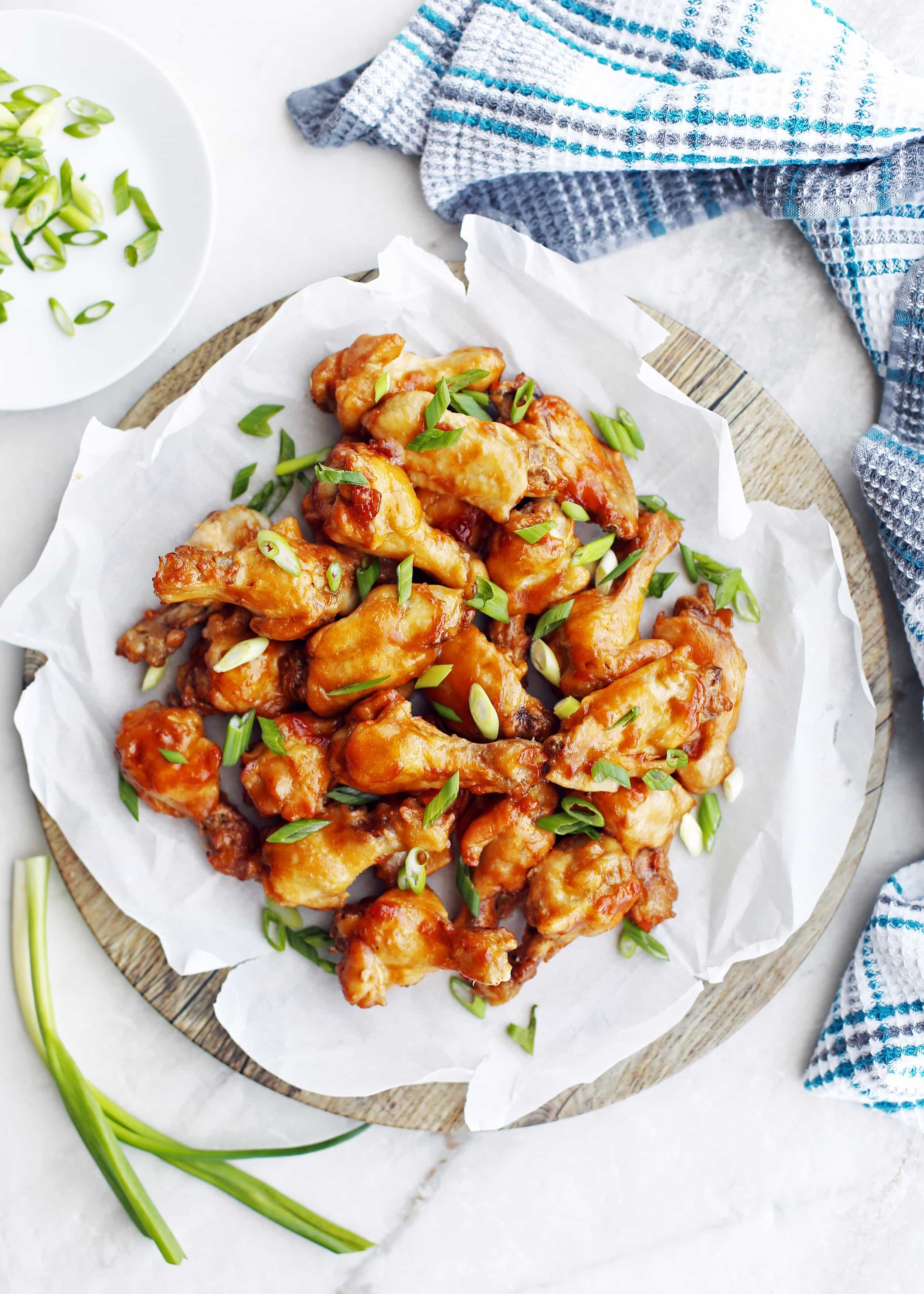 Overhead view of Instant Pot Orange Teriyaki Chicken Wings piled on a parchment paper-topped wooden platter.