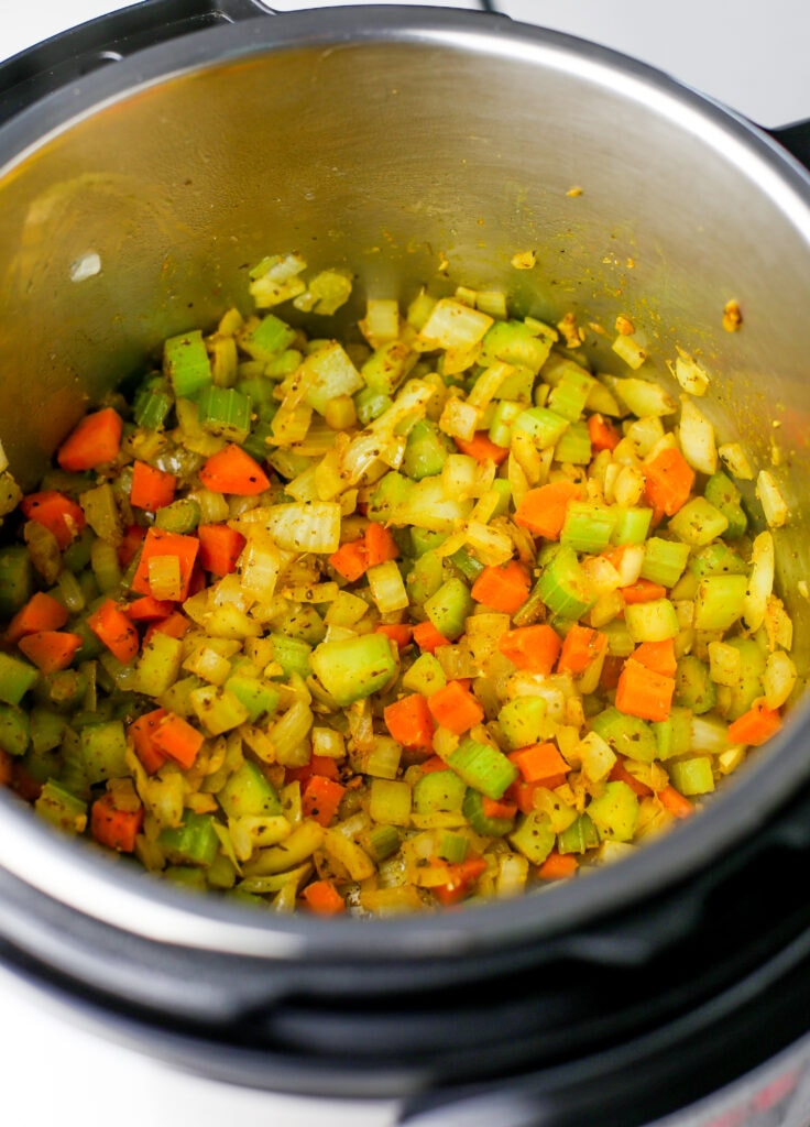 Sautéed diced carrots, onions, and celery with minced garlic and spices in the Instant Pot.