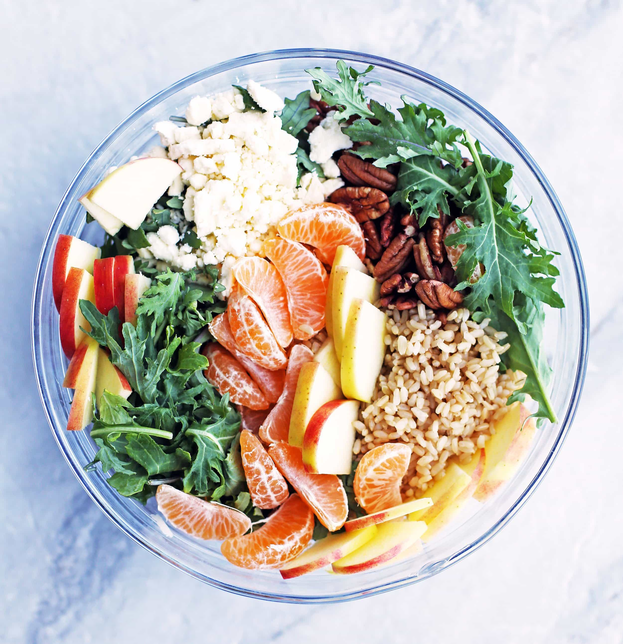 Brown rice, clementine sections, sliced apples, baby kale, and feta cheese in a large glass bowl.