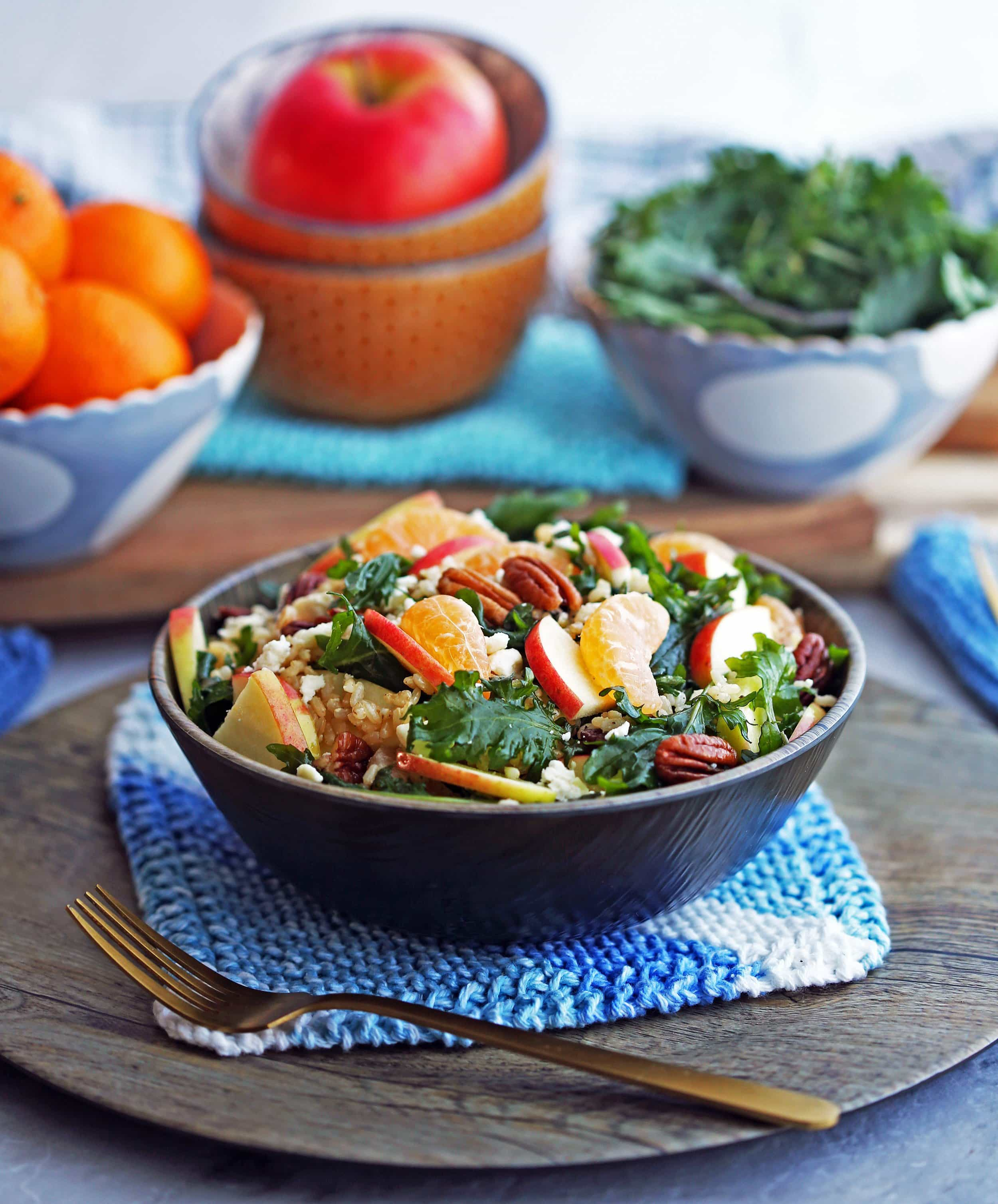 Side angled view of baby kale brown rice salad with feta, apples, and clementines in a wooden bowl, with bowls of clementines, apple, and baby kale in the background.