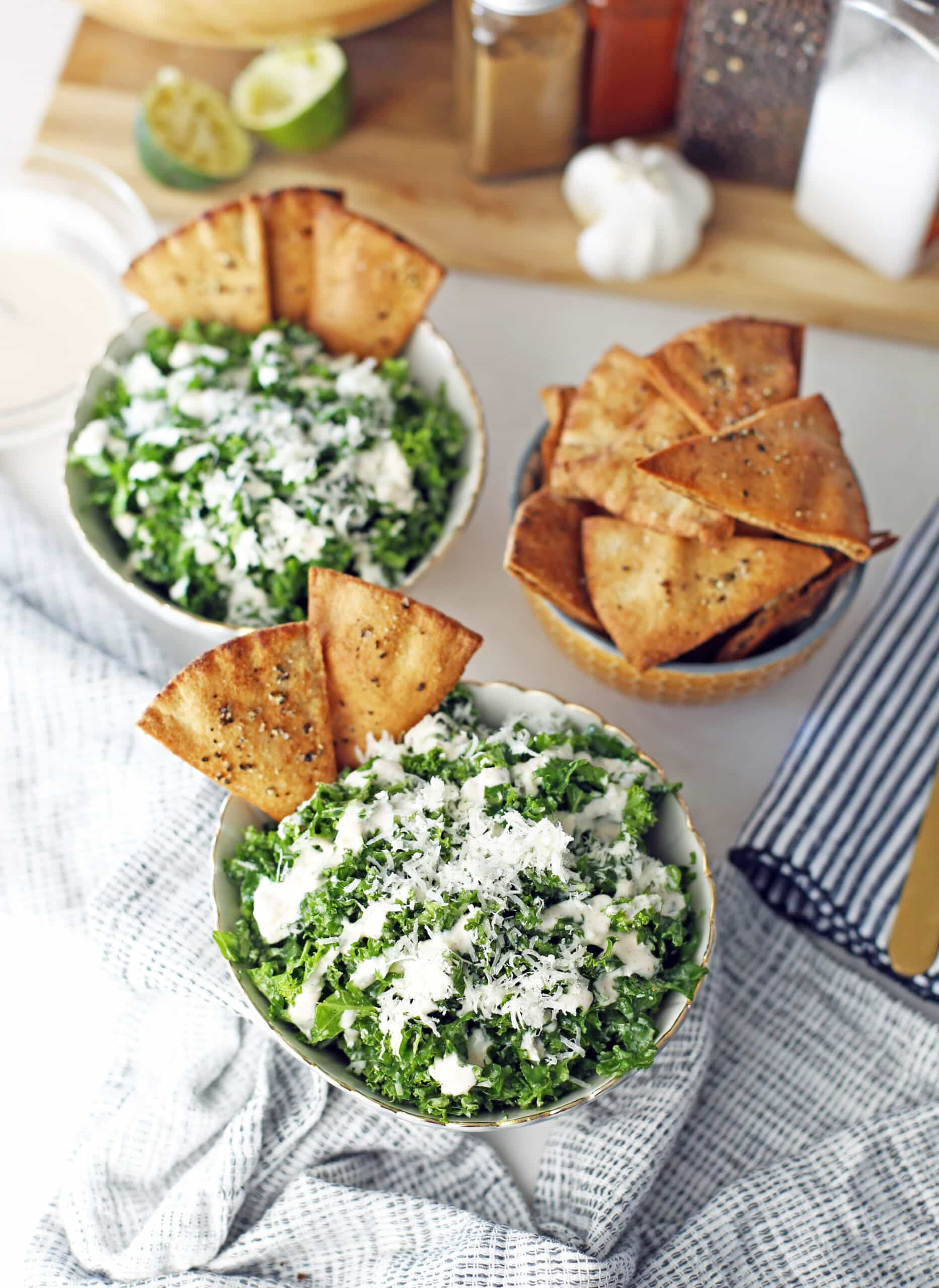 An overhead view of a small bowl of pita chips and two bowls of kale salad topped with pita chips and garlic lime dressing.