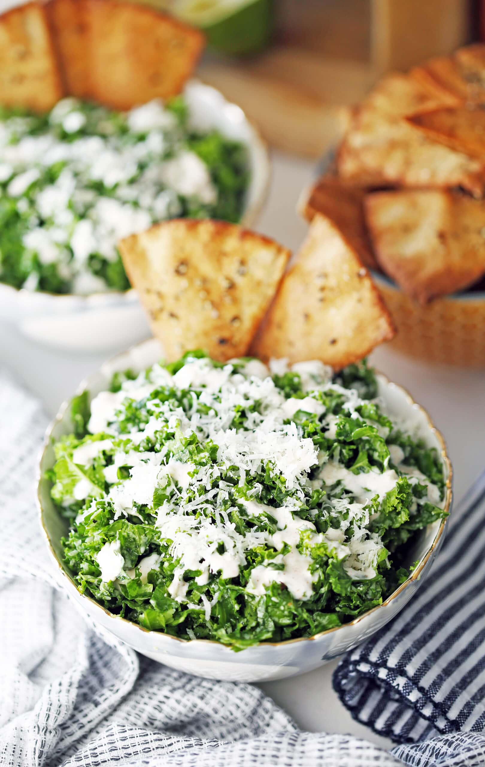 A bowl full of kale salad with parmesan, garlic lime dressing, and pita chips.