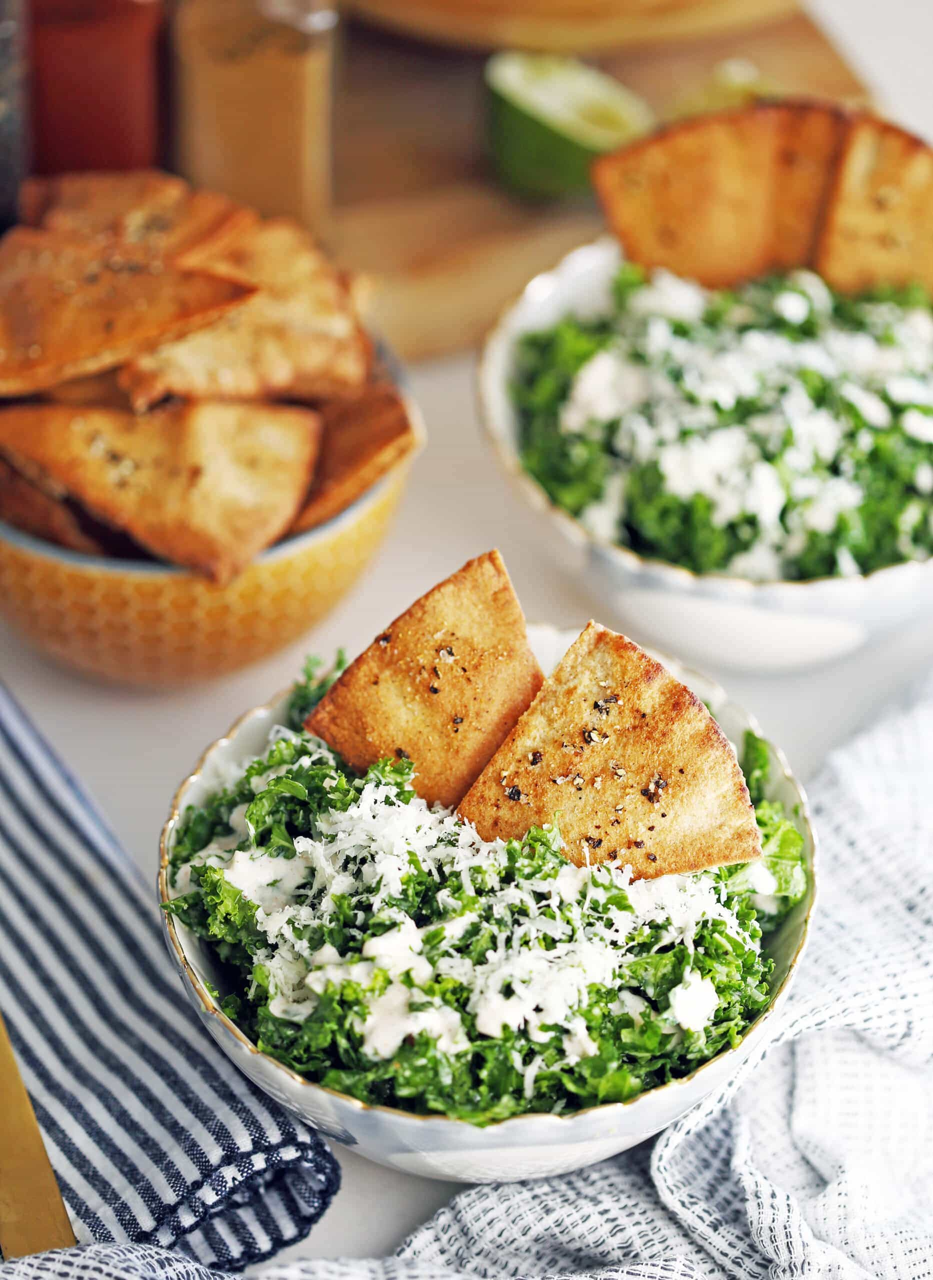Kale parmesan salad with yogurt dressing and pita chips in two bowls and another bowl full of pita chips.