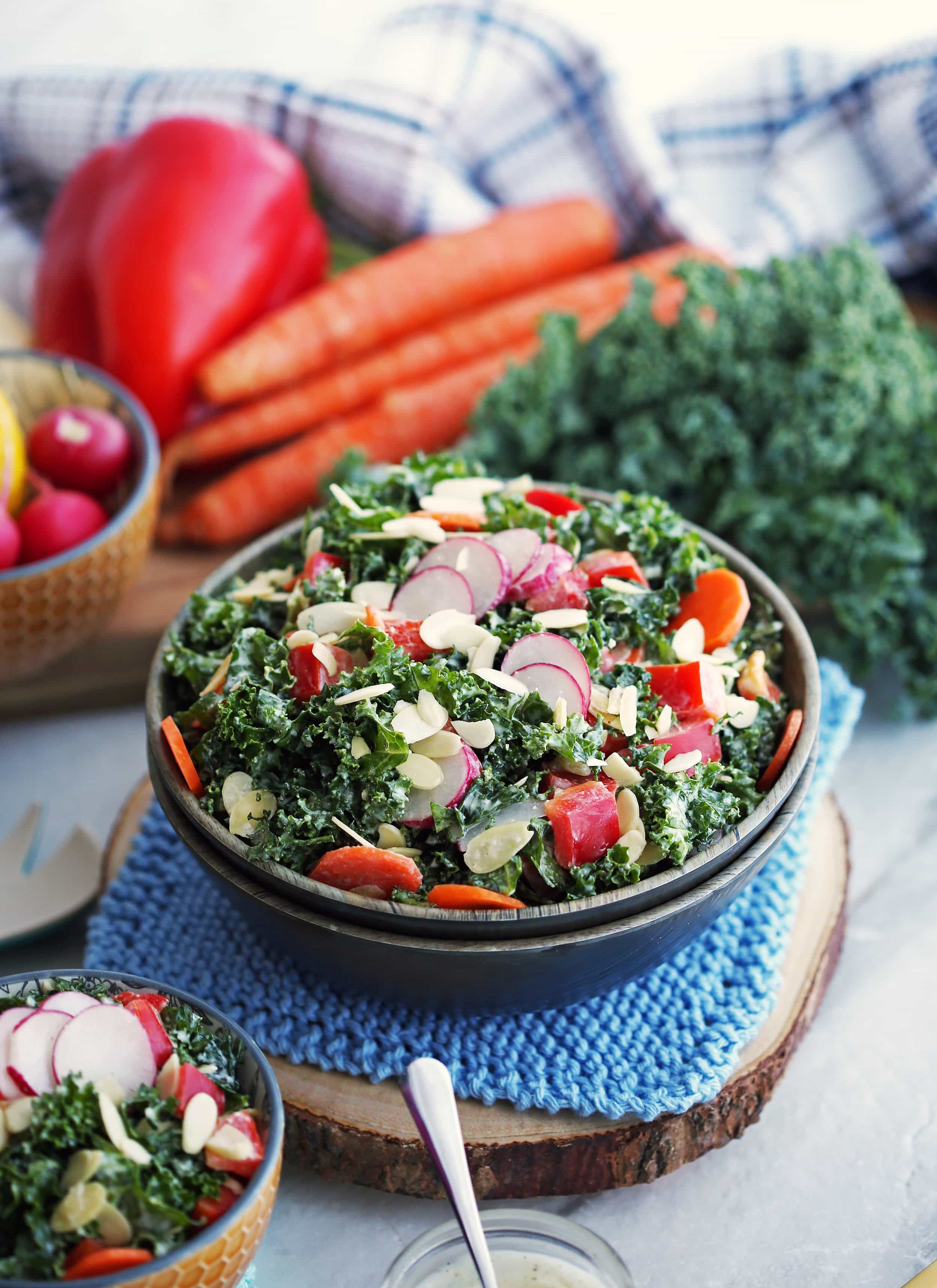 Crunchy salad made with kale, carrots, radishes, peppers, almonds, and parmesan yogurt dressing in a wooden bowl.