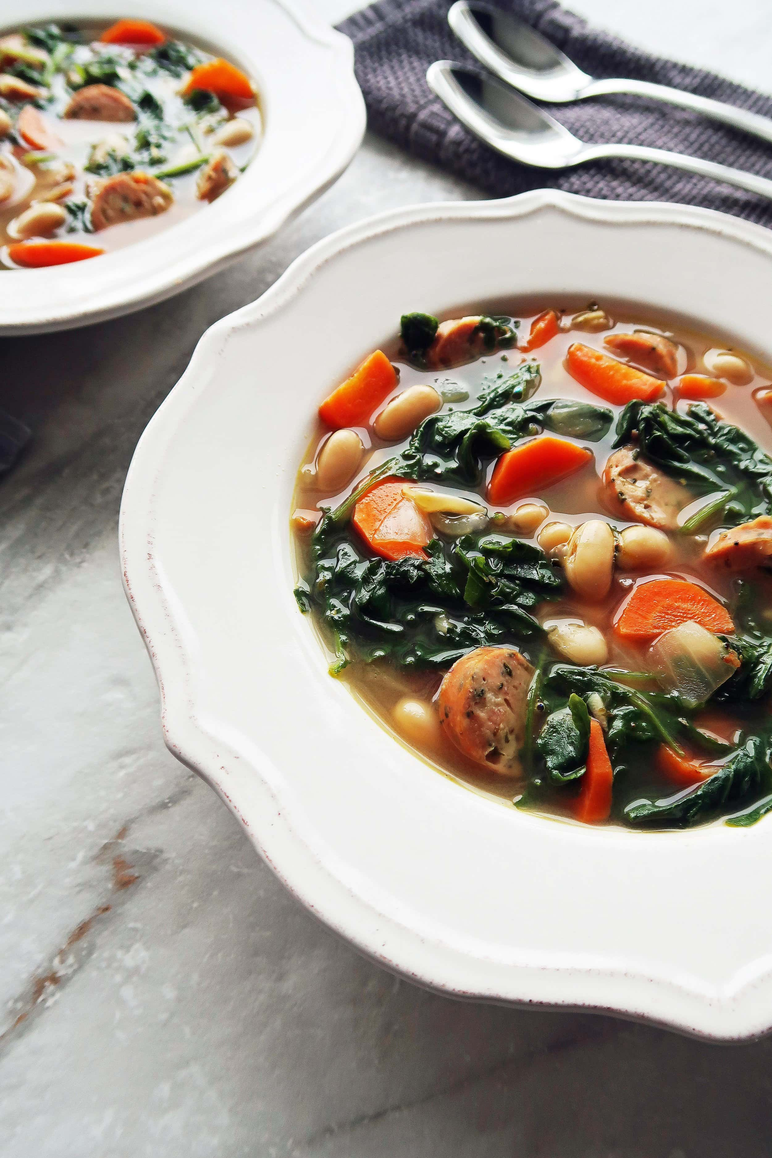 A close up view of Kale, White Bean, and Sausage Soup in a bowl.