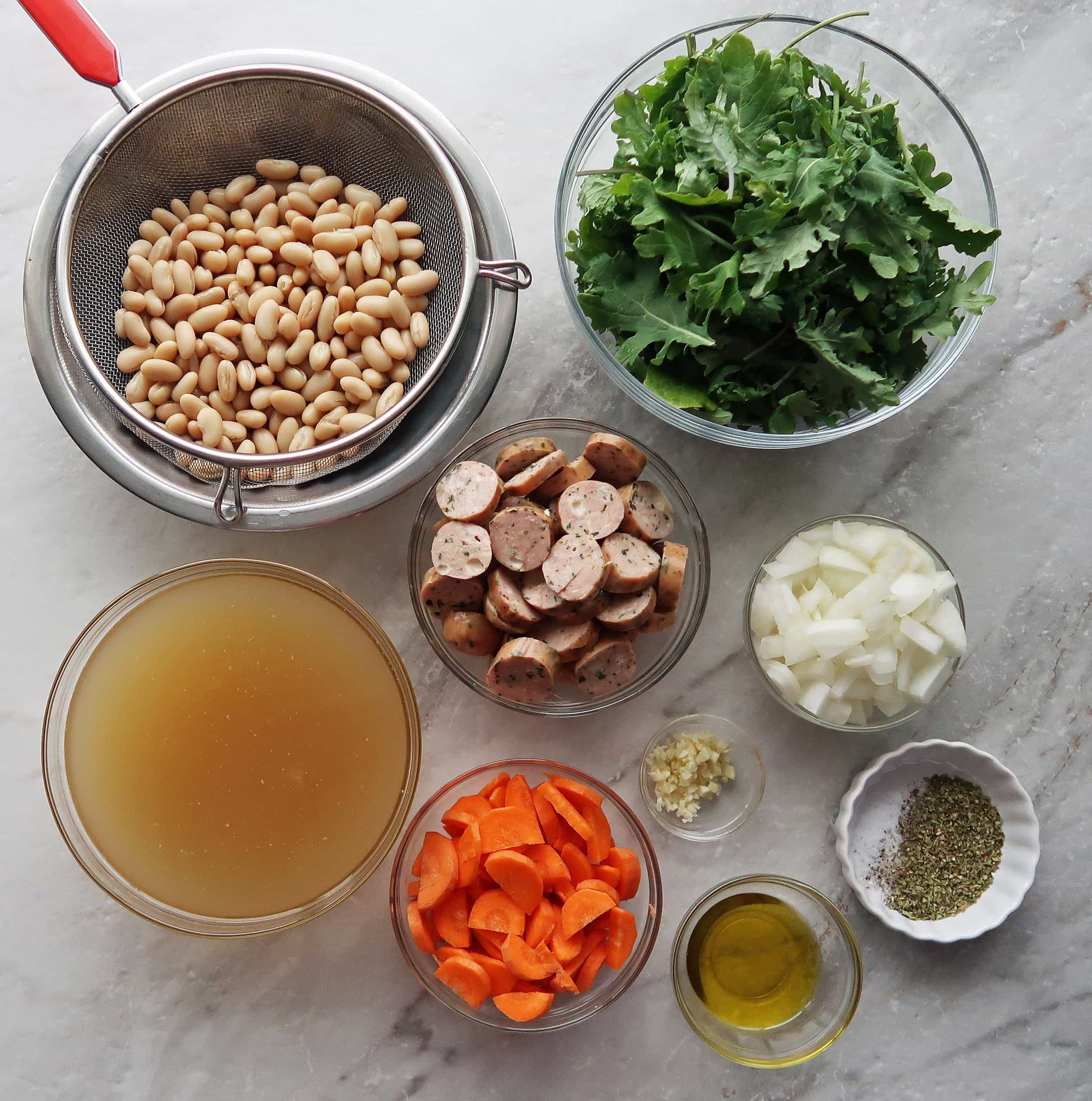 Carrots, onions, sausages slices, white beans, kale, and broth.