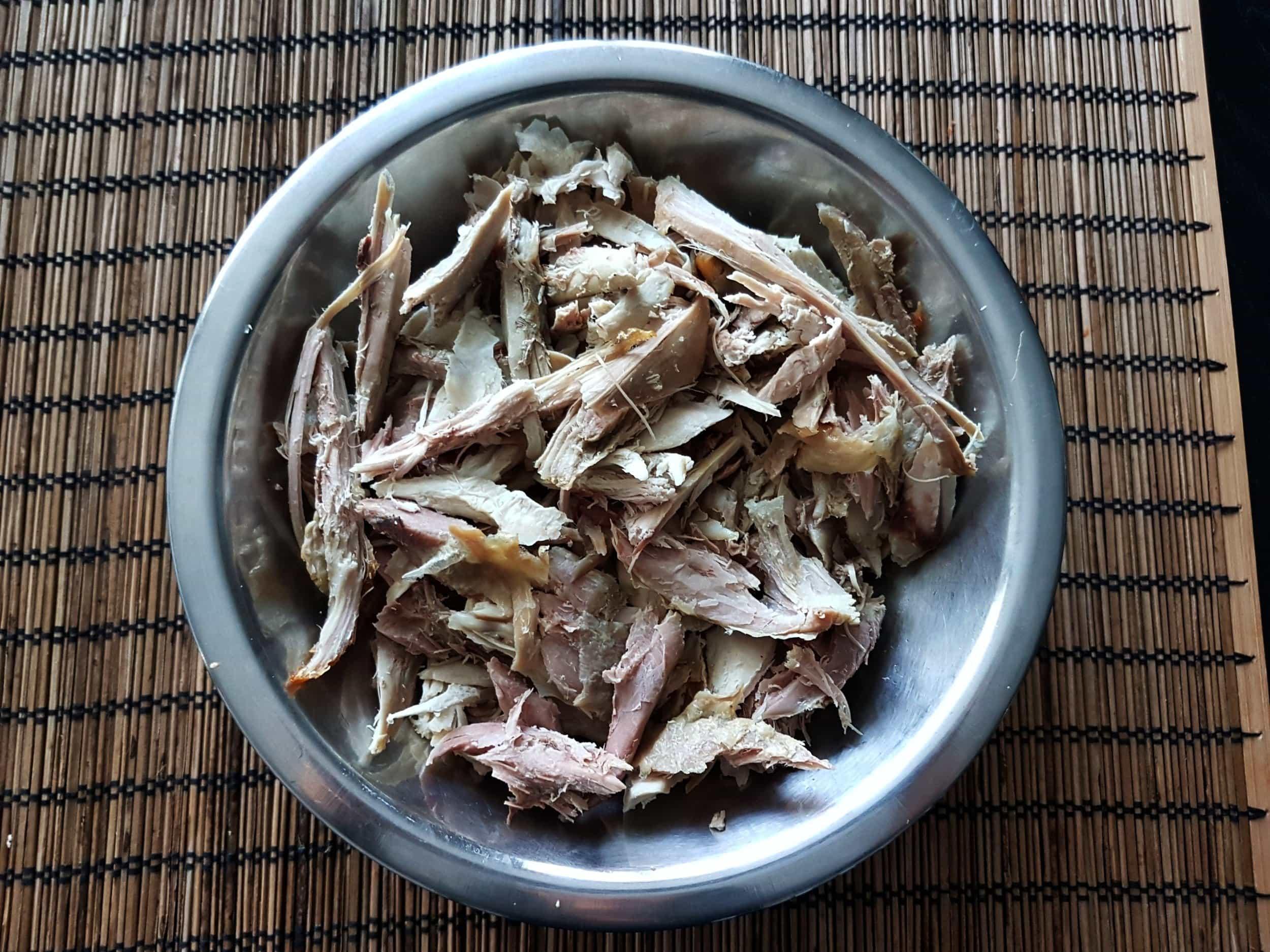 Shredded leftover turkey in a metal bowl.