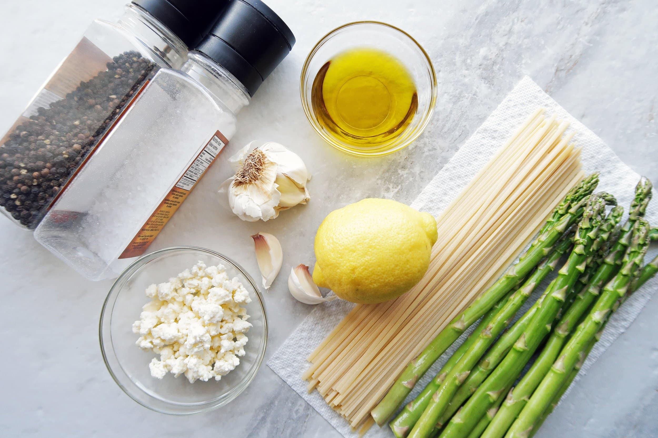 Linguine, feta, asparagus, garlic cloves, a lemon, salt and pepper shakers, and a bowl of olive oil.