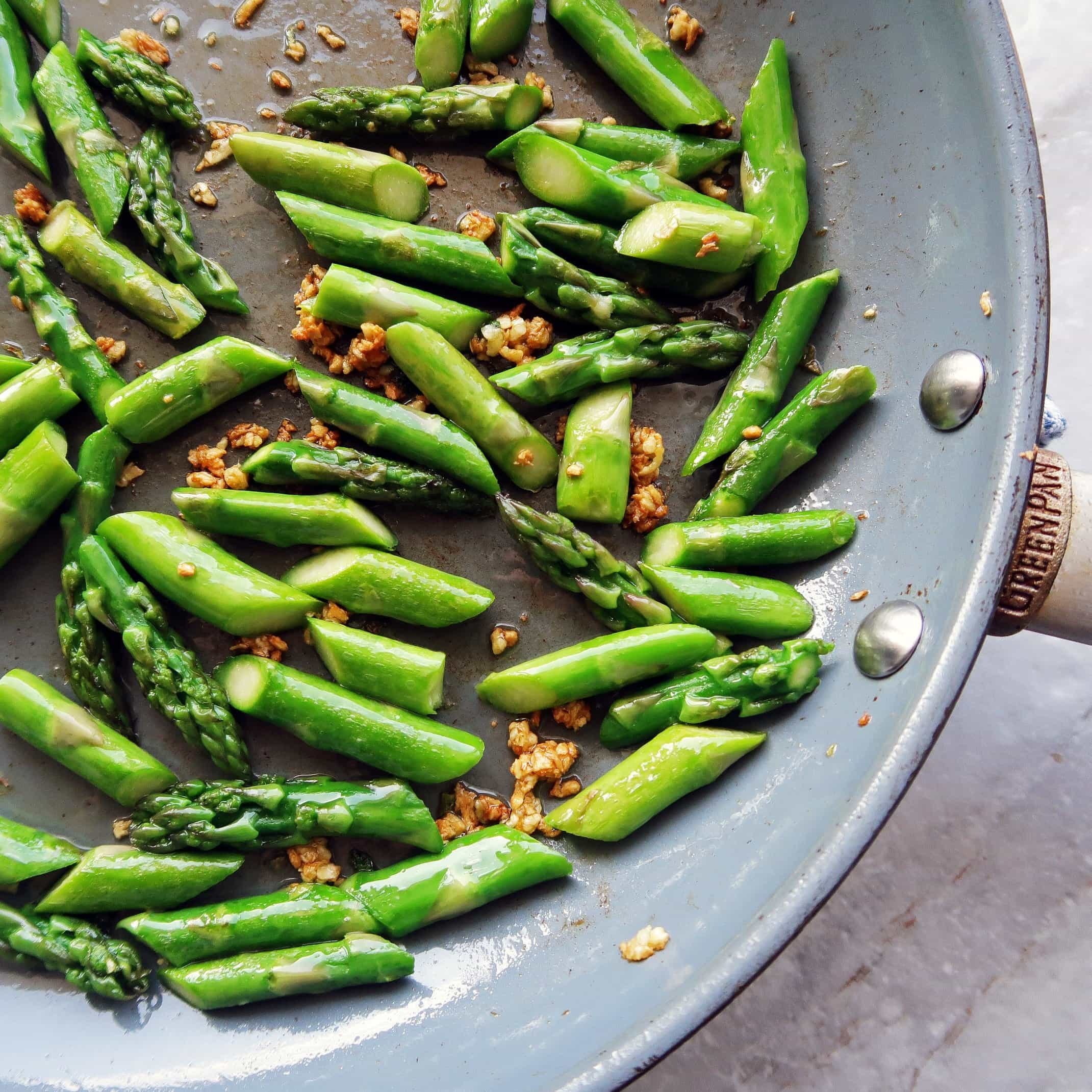 A saute pan featuring sliced asparagus and crispy brown garlic.