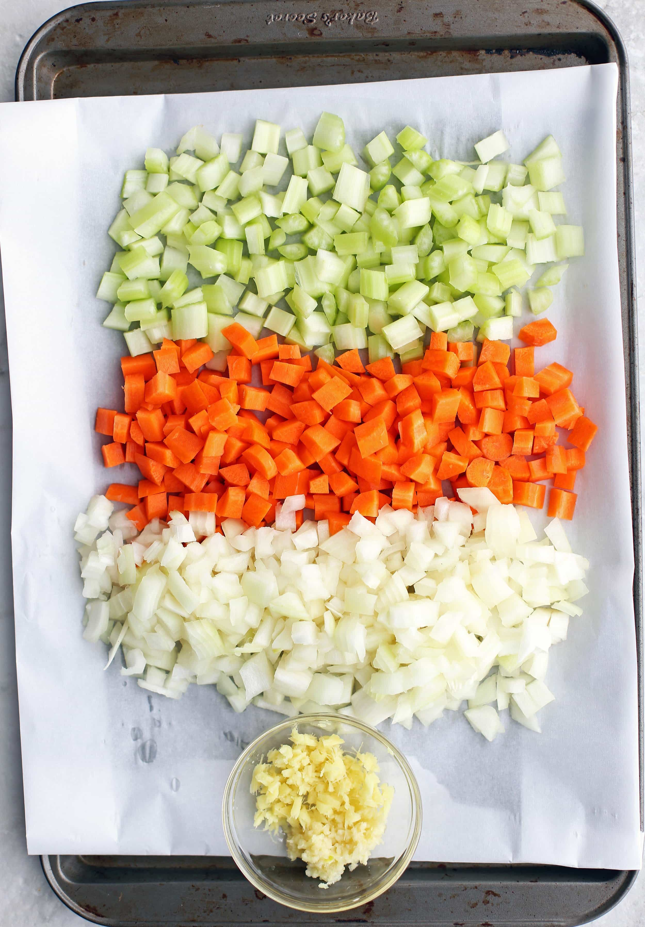 Diced onions, carrots, and celery in a baking sheet; minced garlic and ginger in a small bowl.