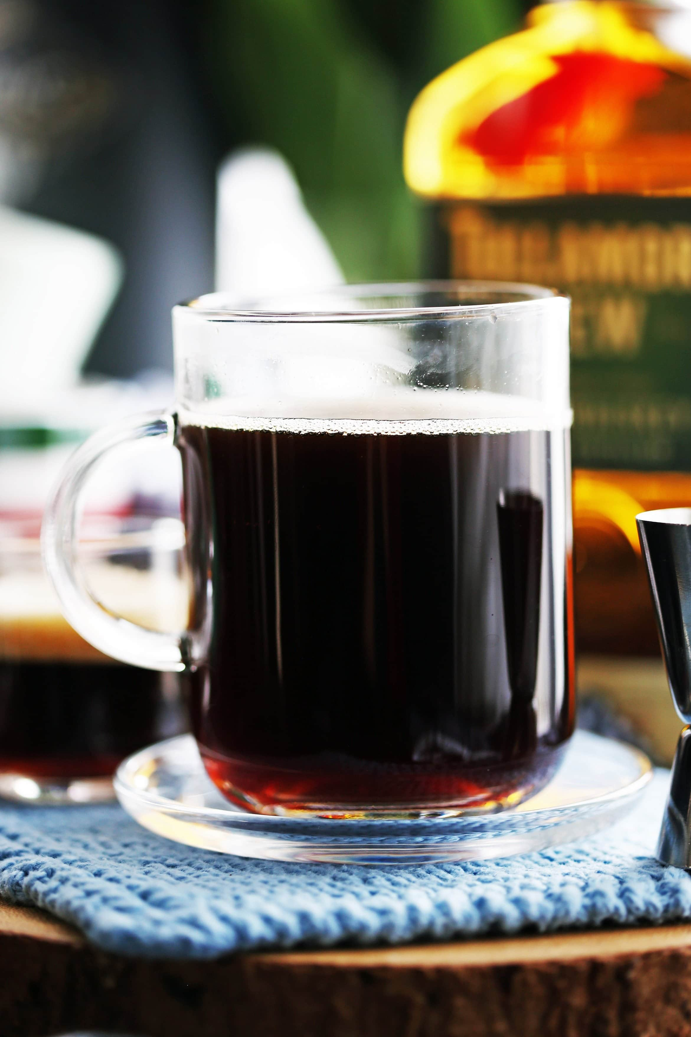 A side view of a glass mug filled with coffee and a small amount of maple syrup and Irish whiskey.