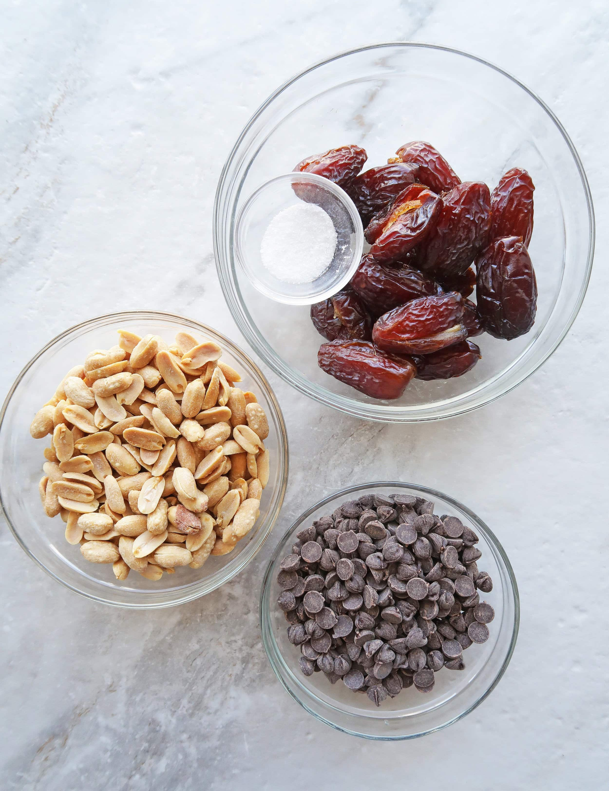 Bowls of roasted salted peanuts, chocolate chips, Medjool dates, and salt.