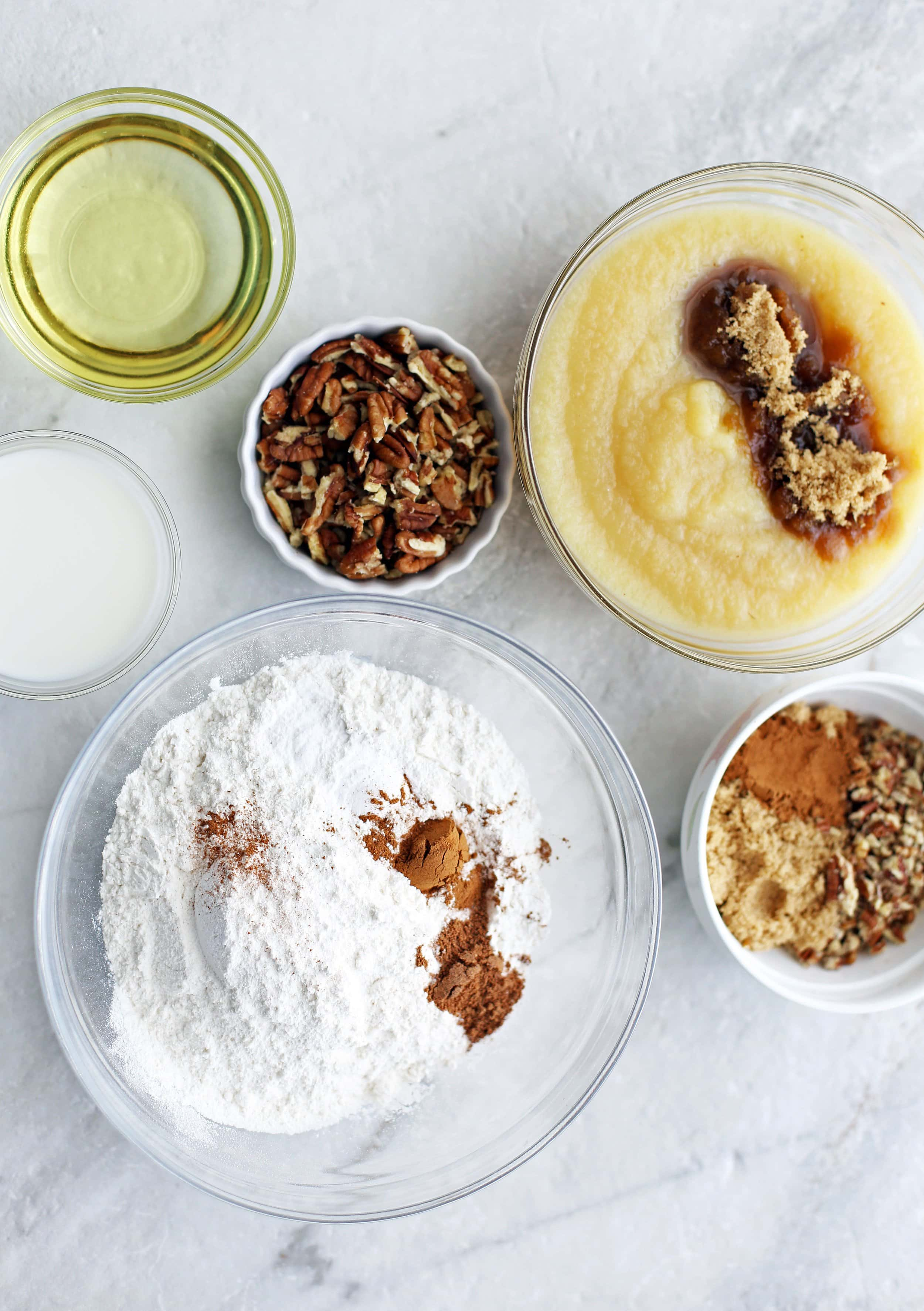 Bowls of applesauce, sugar, spices, pecans, milk, and baking soda.