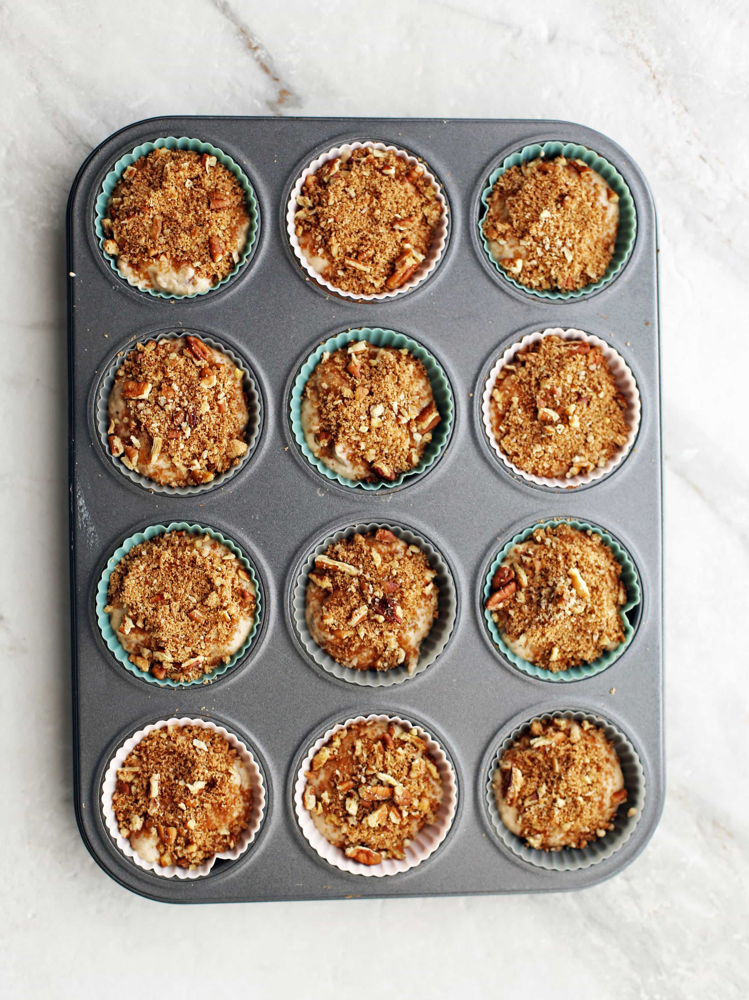 Pre-baked cinnamon pecan applesauce muffins in a muffin baking pan.