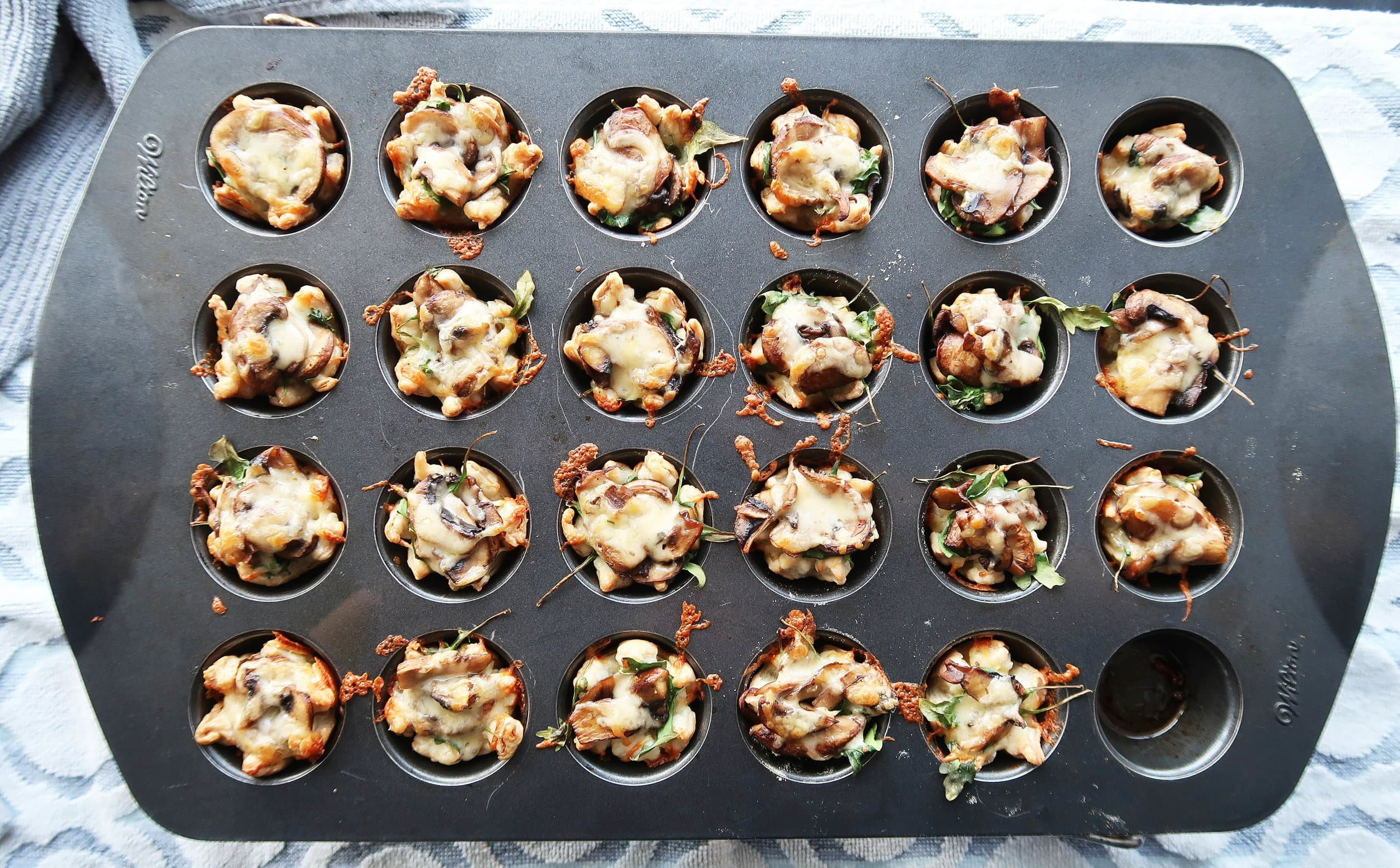 Mushroom Arugula Cheese Tarts in a muffin pan.