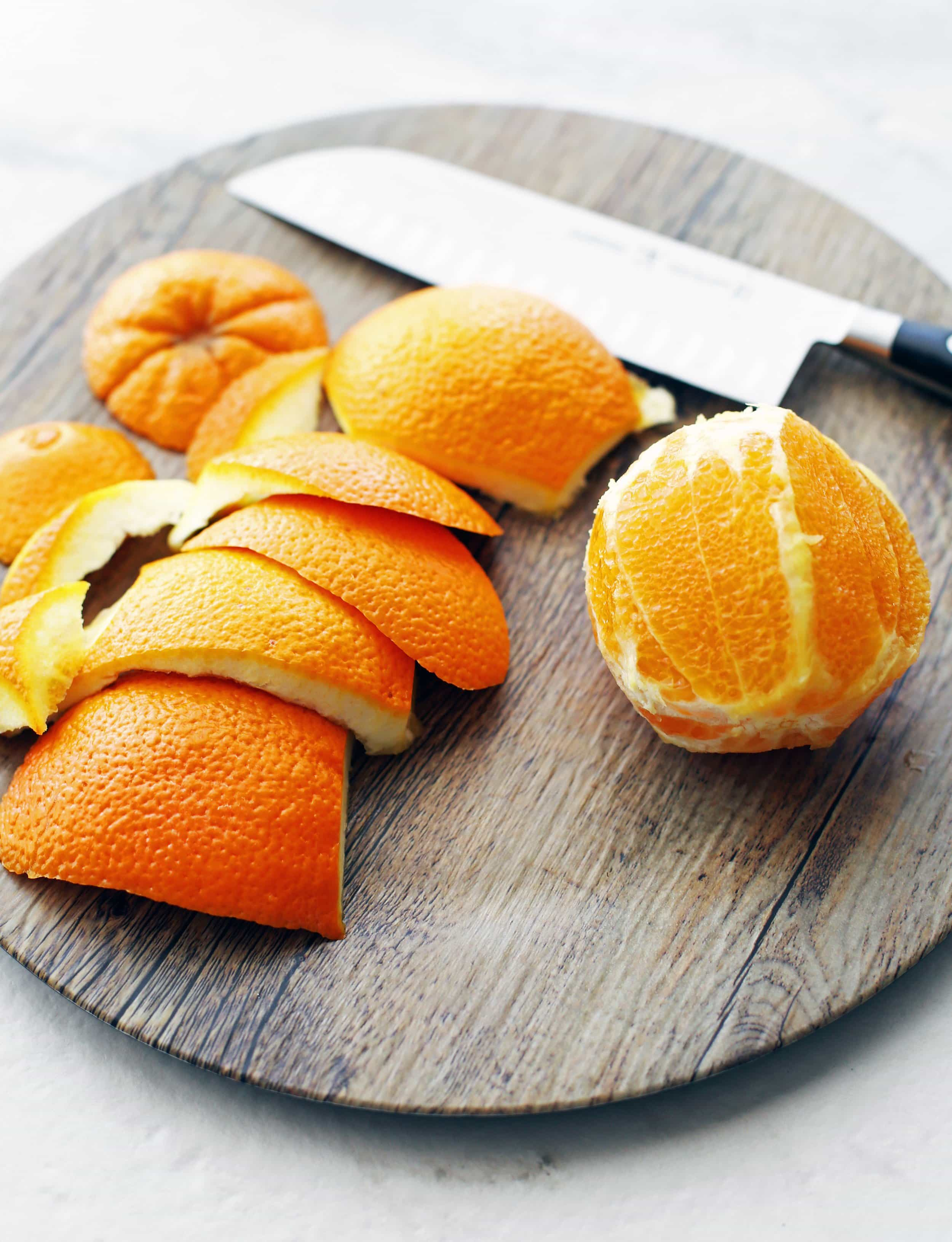 A cut and peeled navel orange and a large knife on a wooden platter.