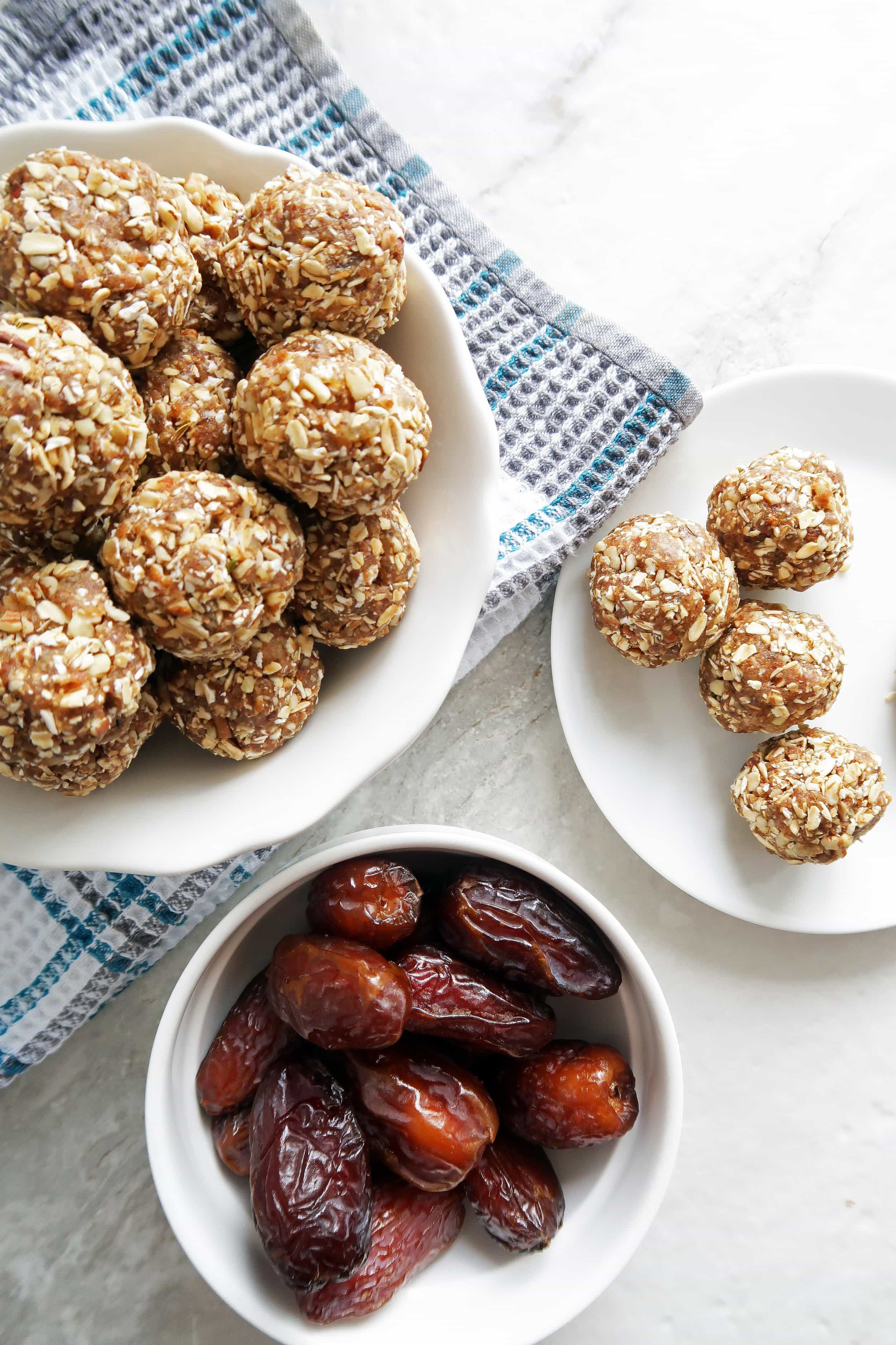 No Bake Chai Spiced Date Energy Balls pilled in a white bowl, energy balls on a white plate, and a bowl of dates to its side.