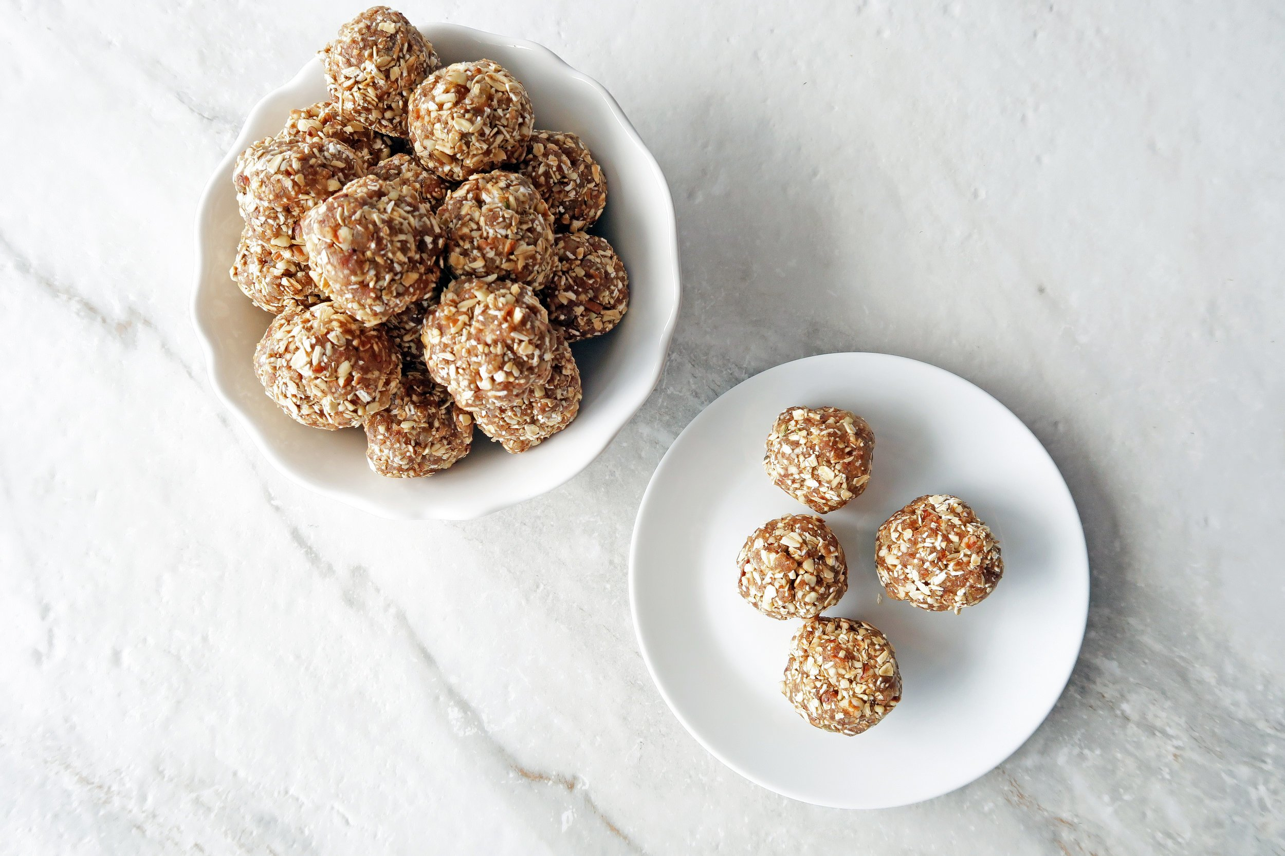 No Bake Chai Spiced Date Energy Balls piled in a white bowl with four energy balls on a white plate to its side.