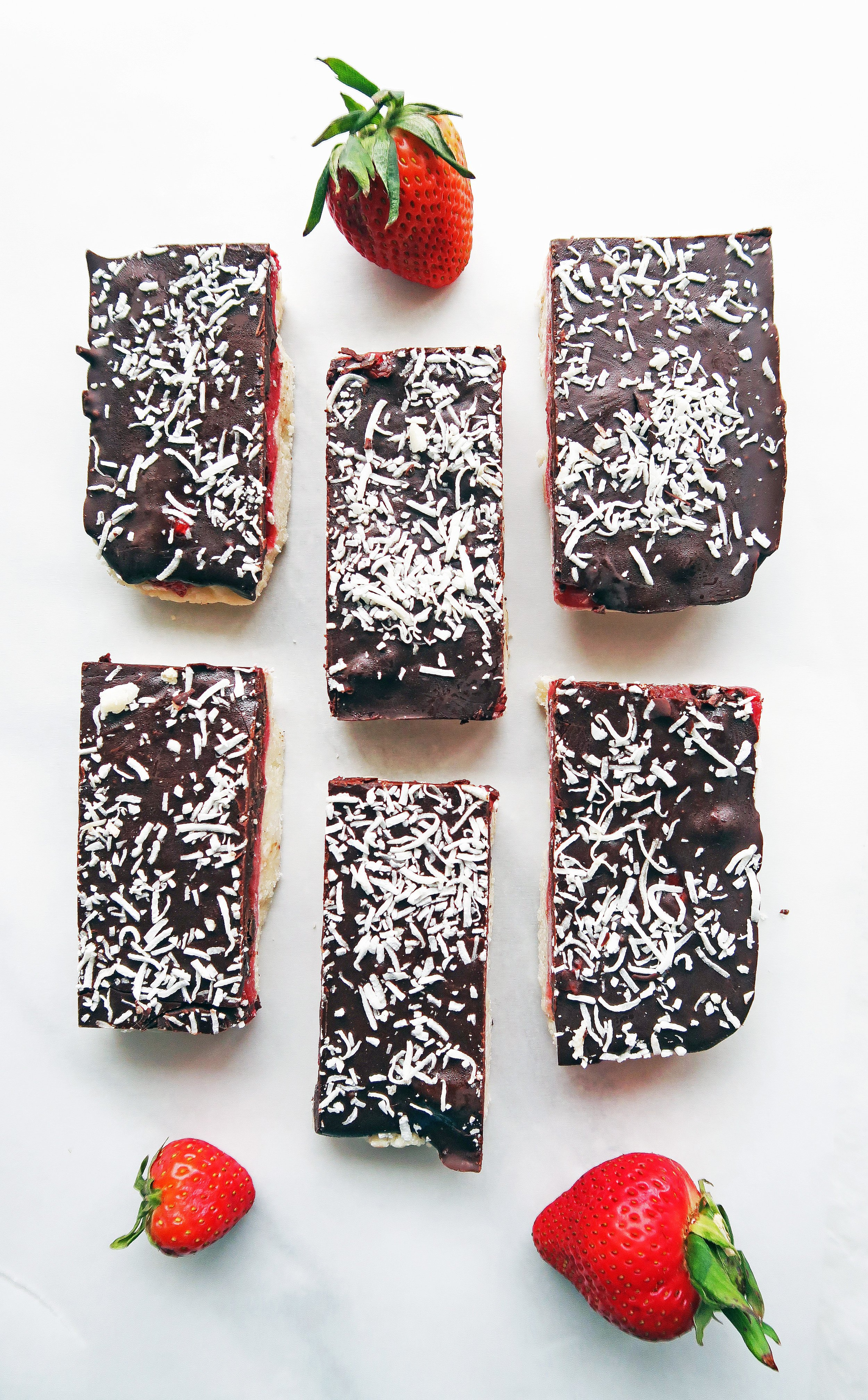 No-Bake, vegan, and gluten-free Chocolate Strawberry Coconut Bars on parchment paper with strawberries around them.