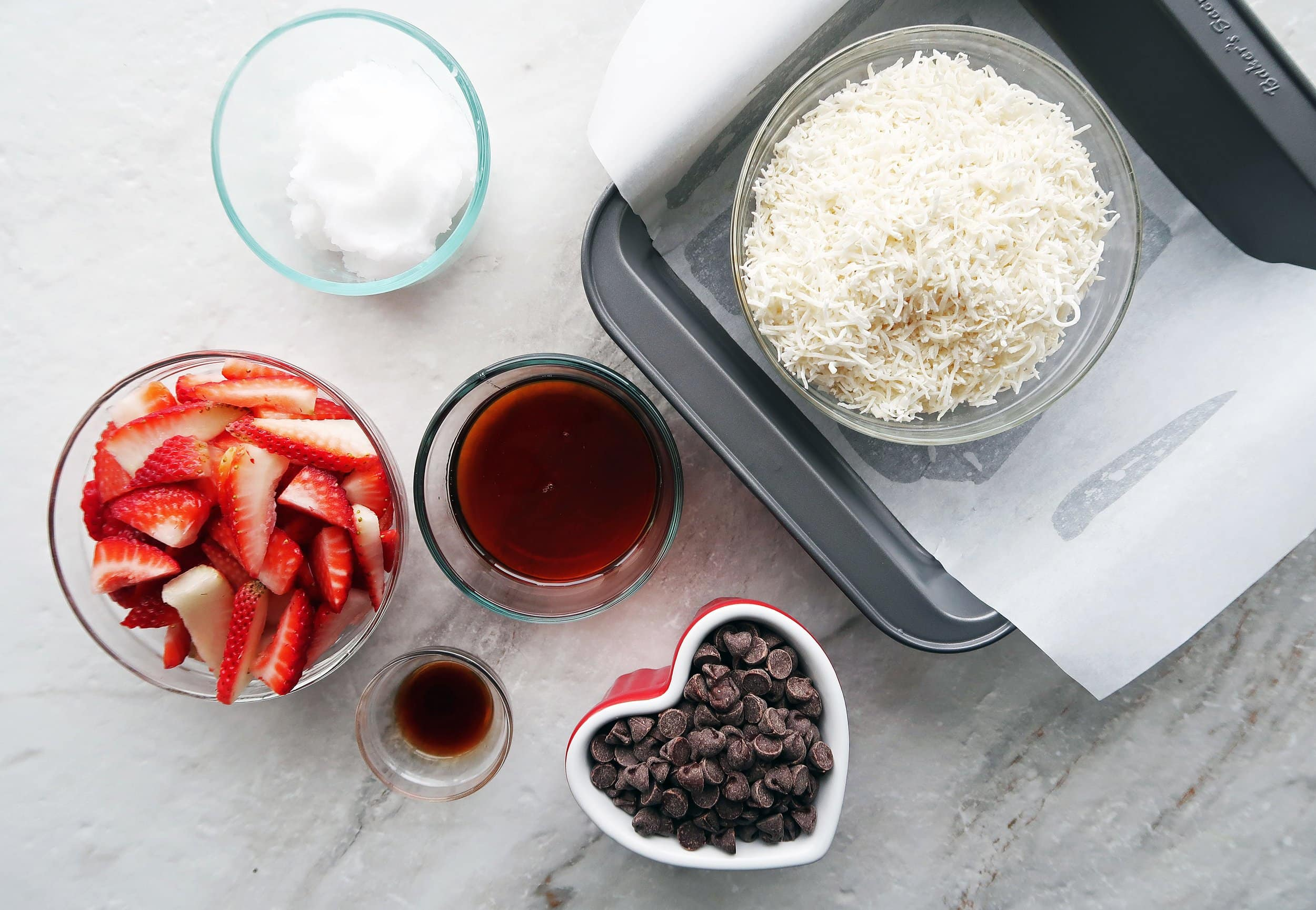 Bowls of strawberries, chocolate chips, maple syrup,and shredded coconut.