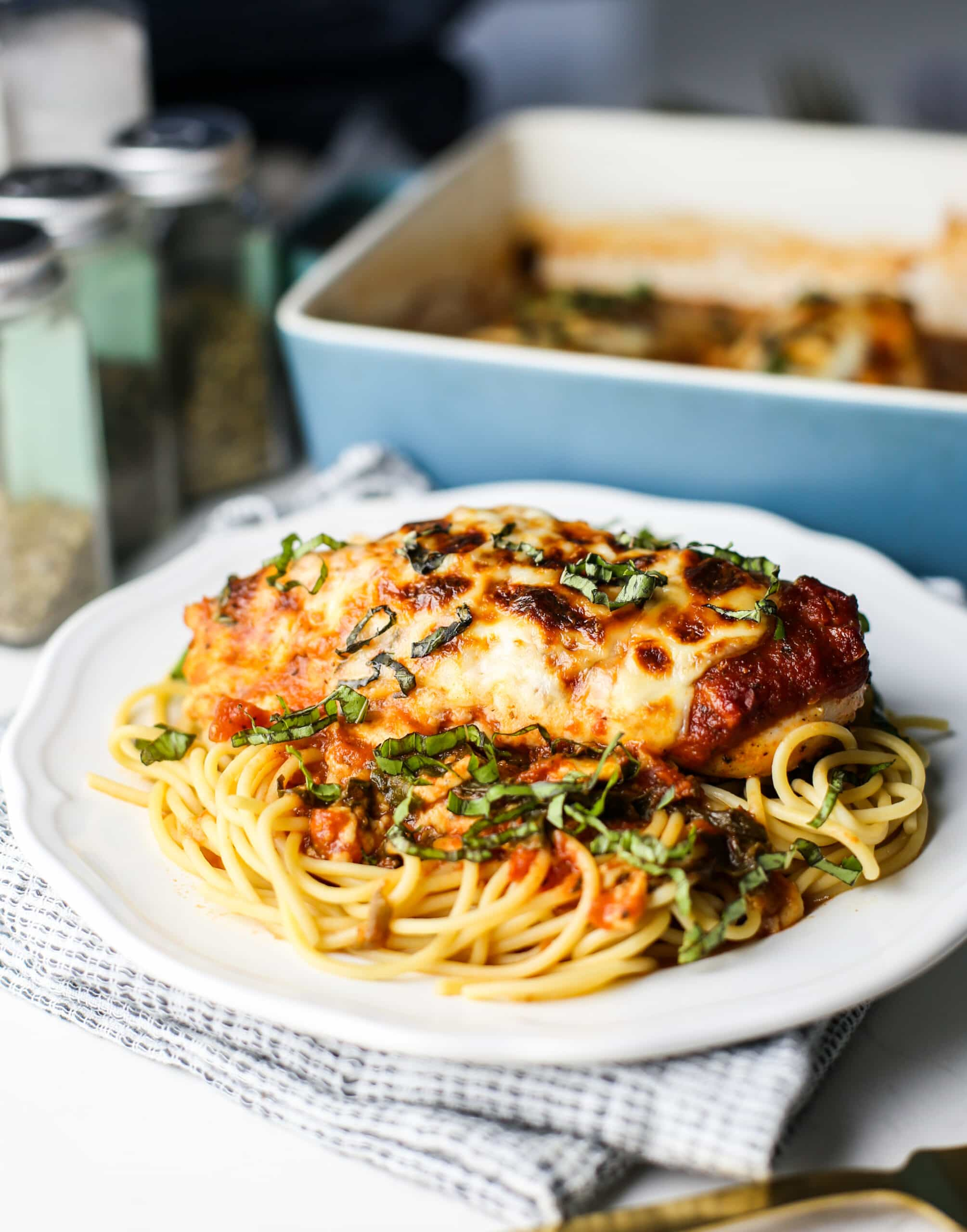A side view of baked chicken with mozzeralla and marinara sauce on top of spaghetti in a white plate.