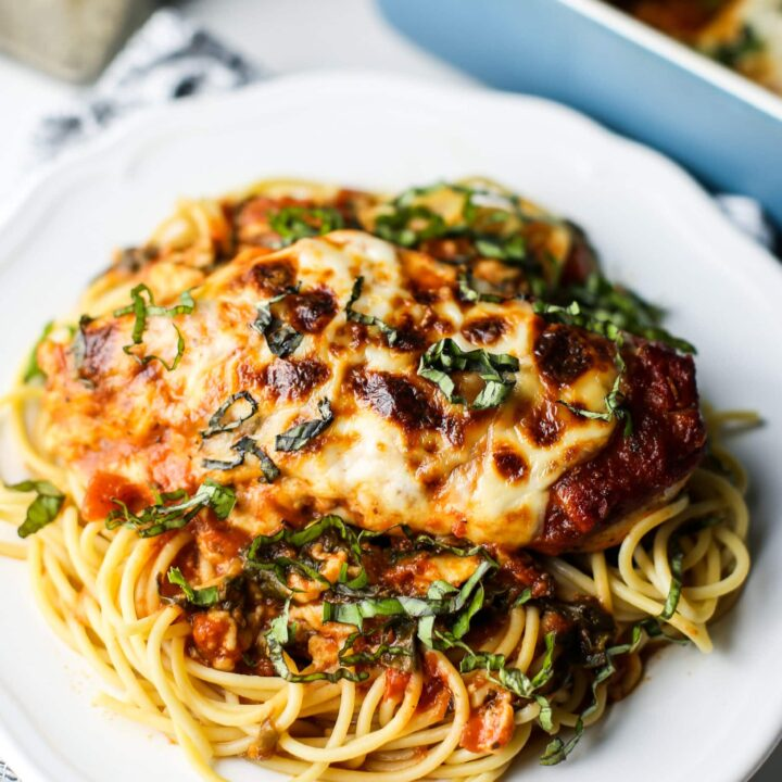 A close-up view of mozzarella chicken with marinara sauce and spaghetti on a white plate.