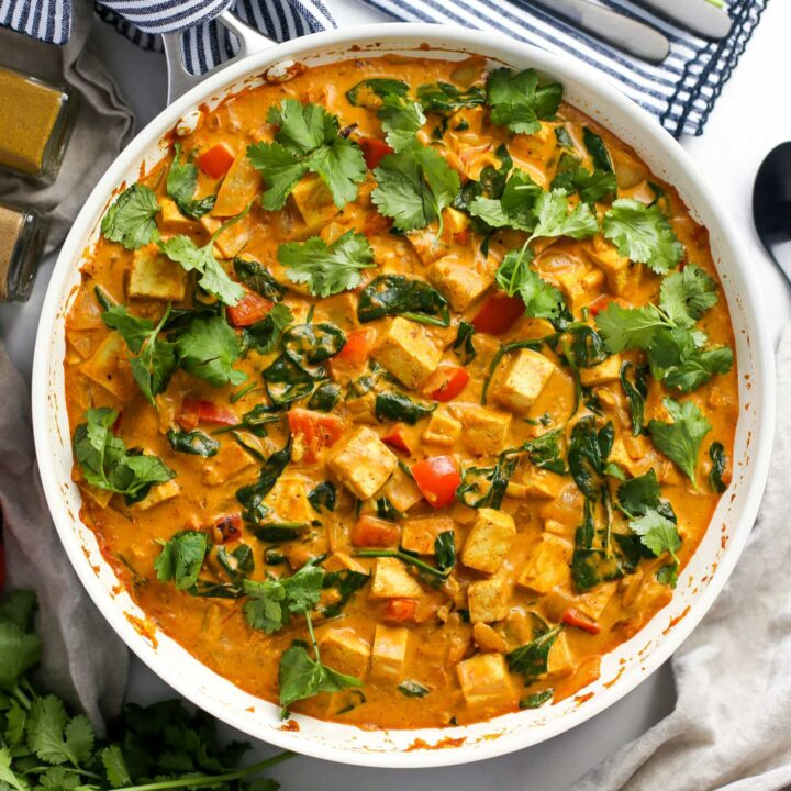 Overhead view of creamy and colourful tofu coconut curry in a large white skillet.