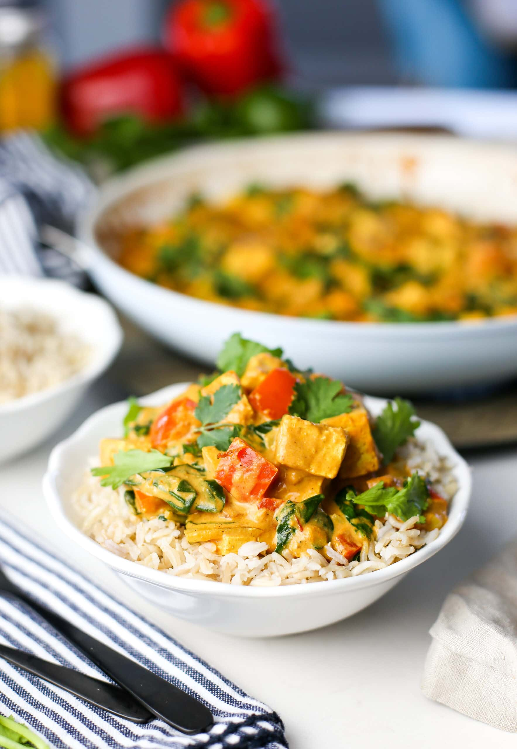 Creamy tofu coconut curry with brown rice in a white bowl.