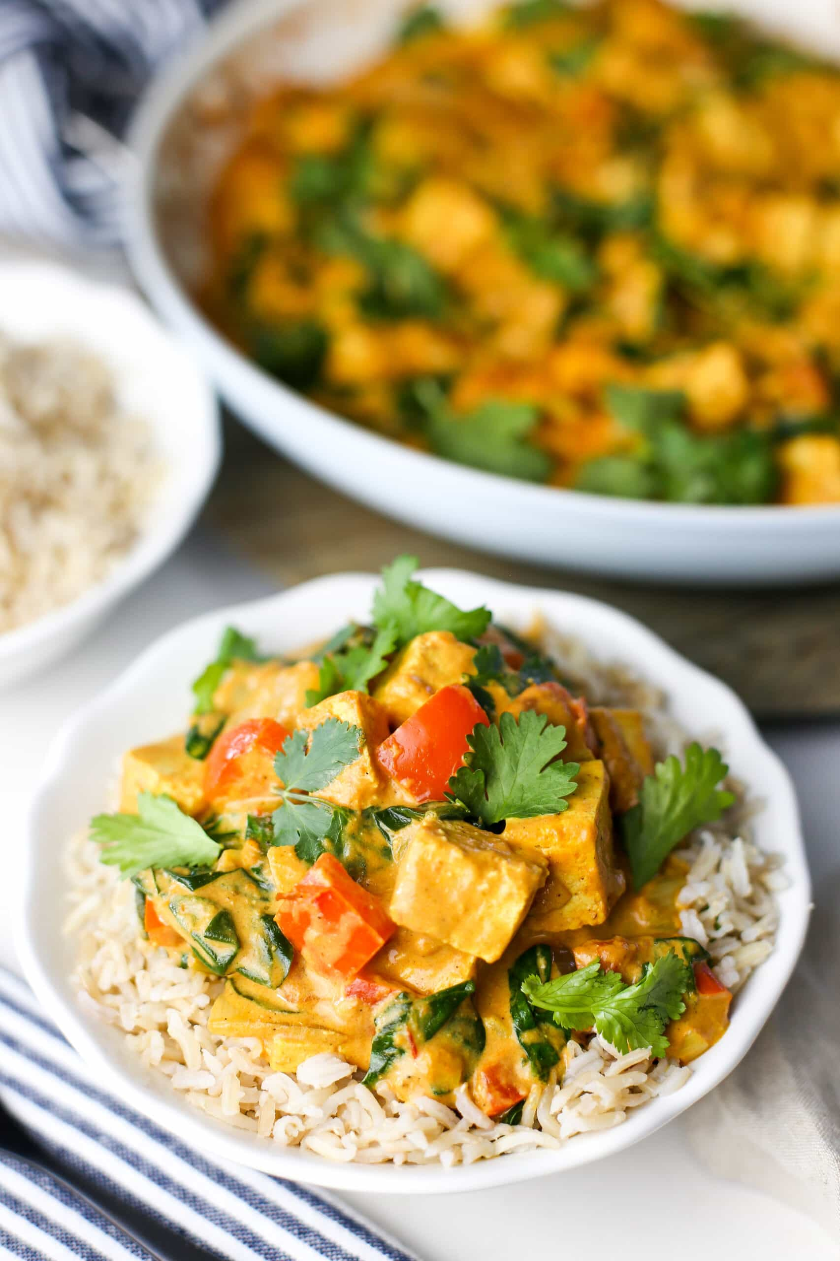 Delicious tofu coconut curry with fresh cilantro on top of brown rice in a white bowl.