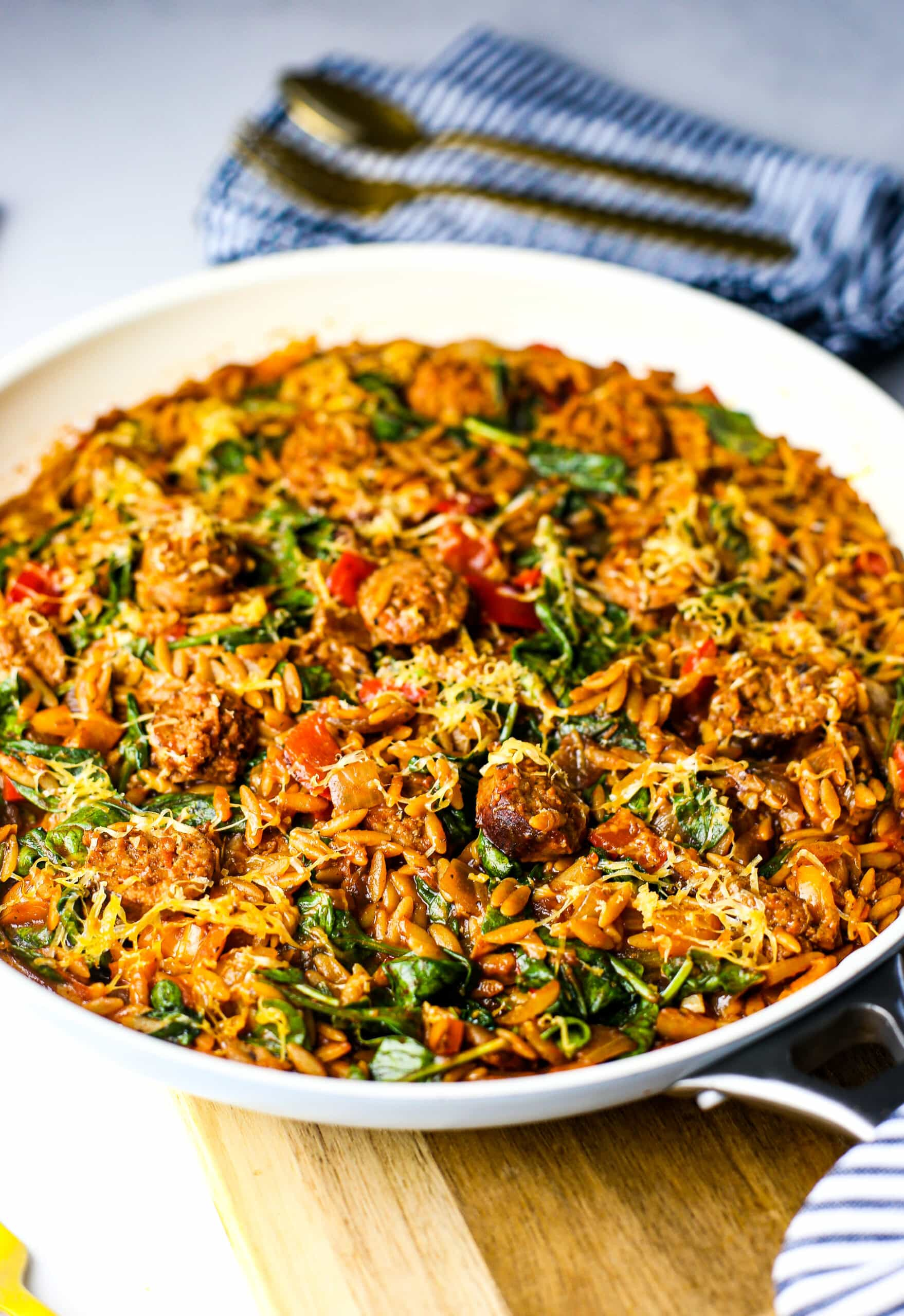 A top-angled view of a white frying pan full of orzo pasta with Italian sausage, onions, and peppers in a marinara sauce.